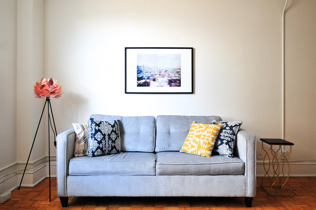 Gray couch with decorative pillows and unique art in a cozy apartment living room