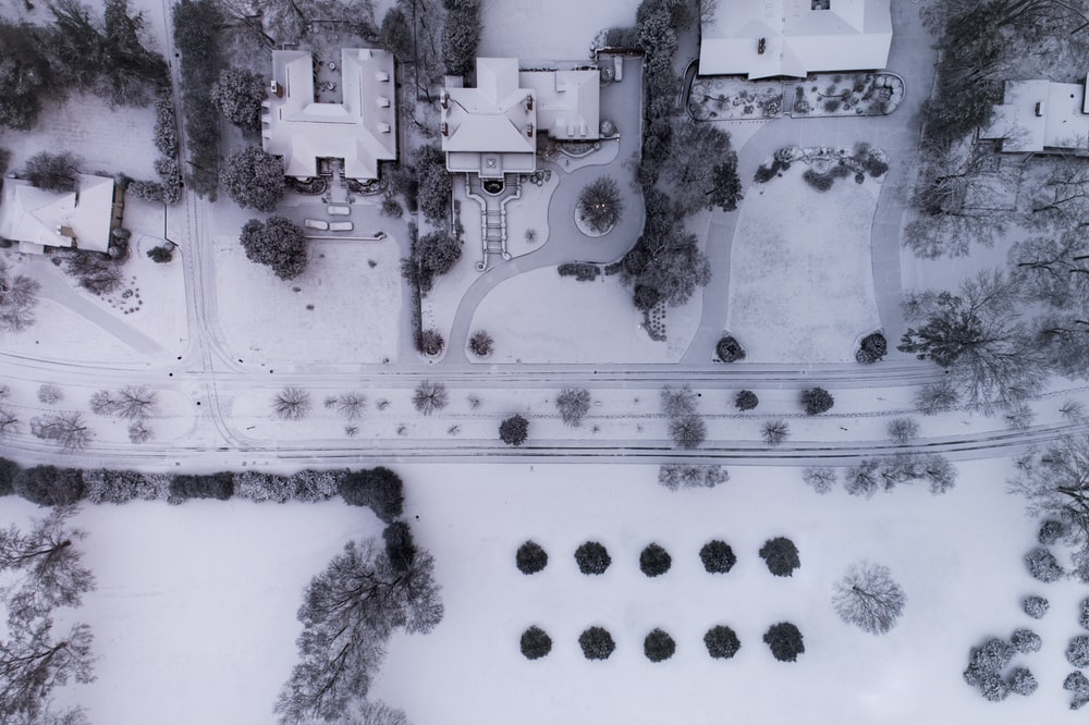 aerial photography of snow capped field near buildings