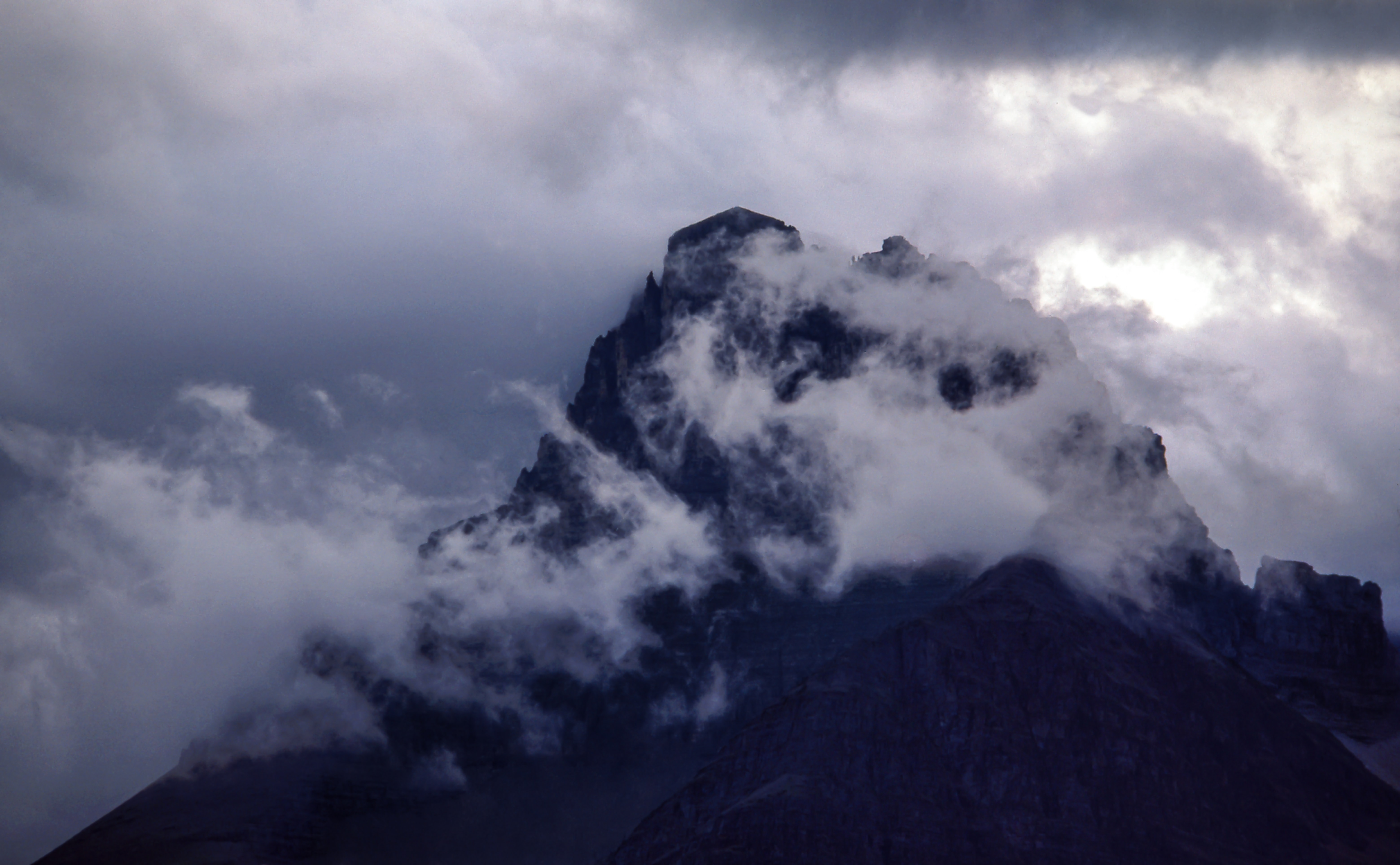 A jagged mountain peak shrouded in patchy clouds