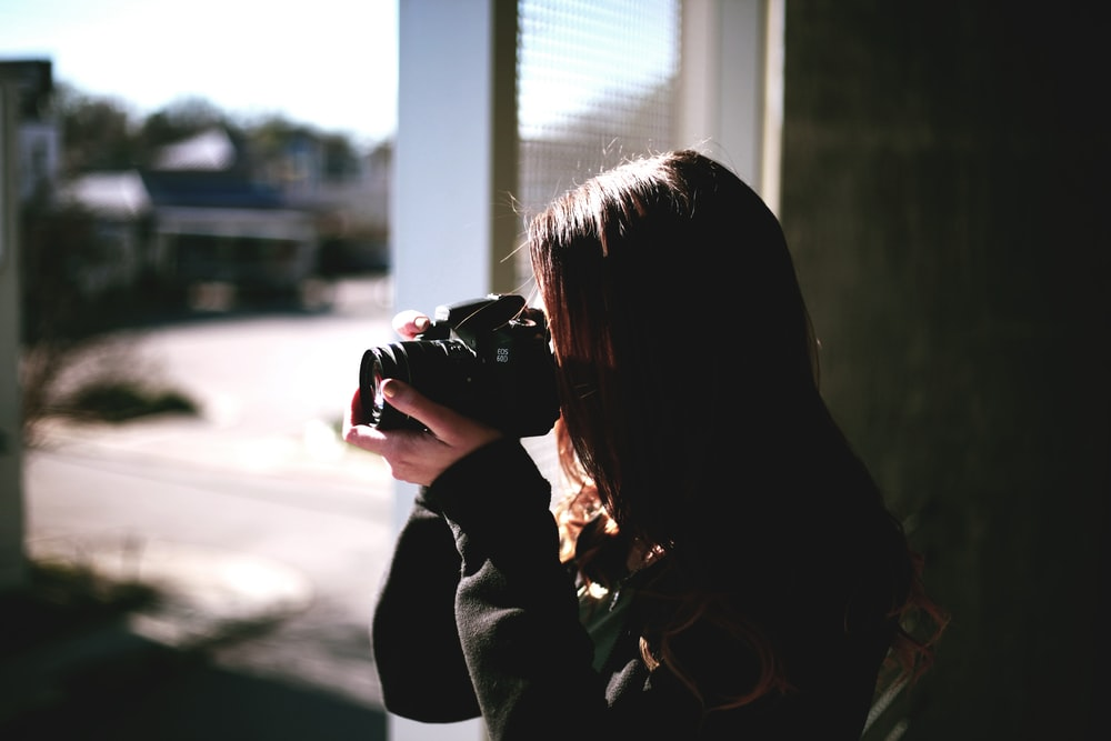 A woman with brown hair focuses her camera out a window in Memphis