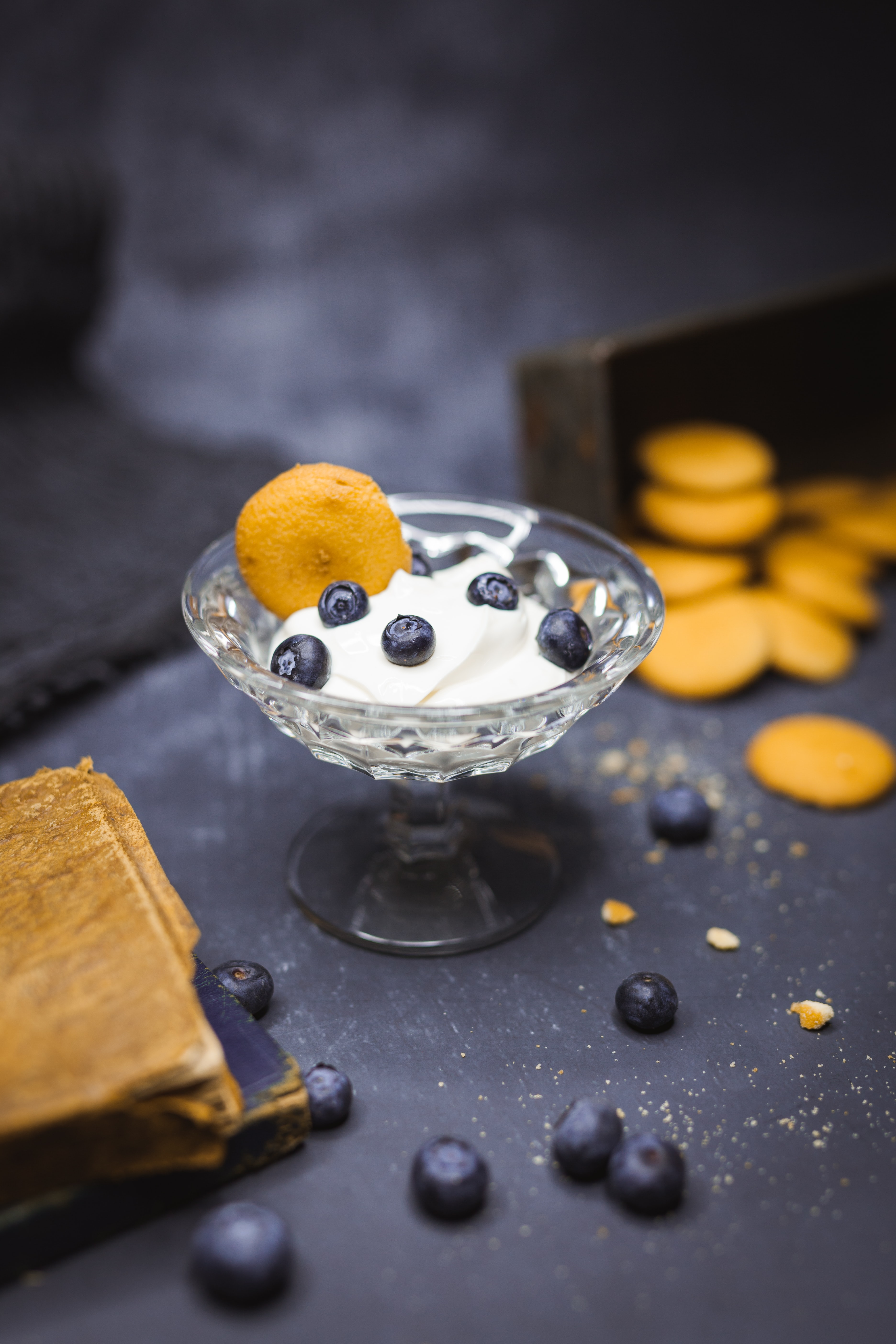 shallow focus photography of yoghurt in glass with blueberries on top