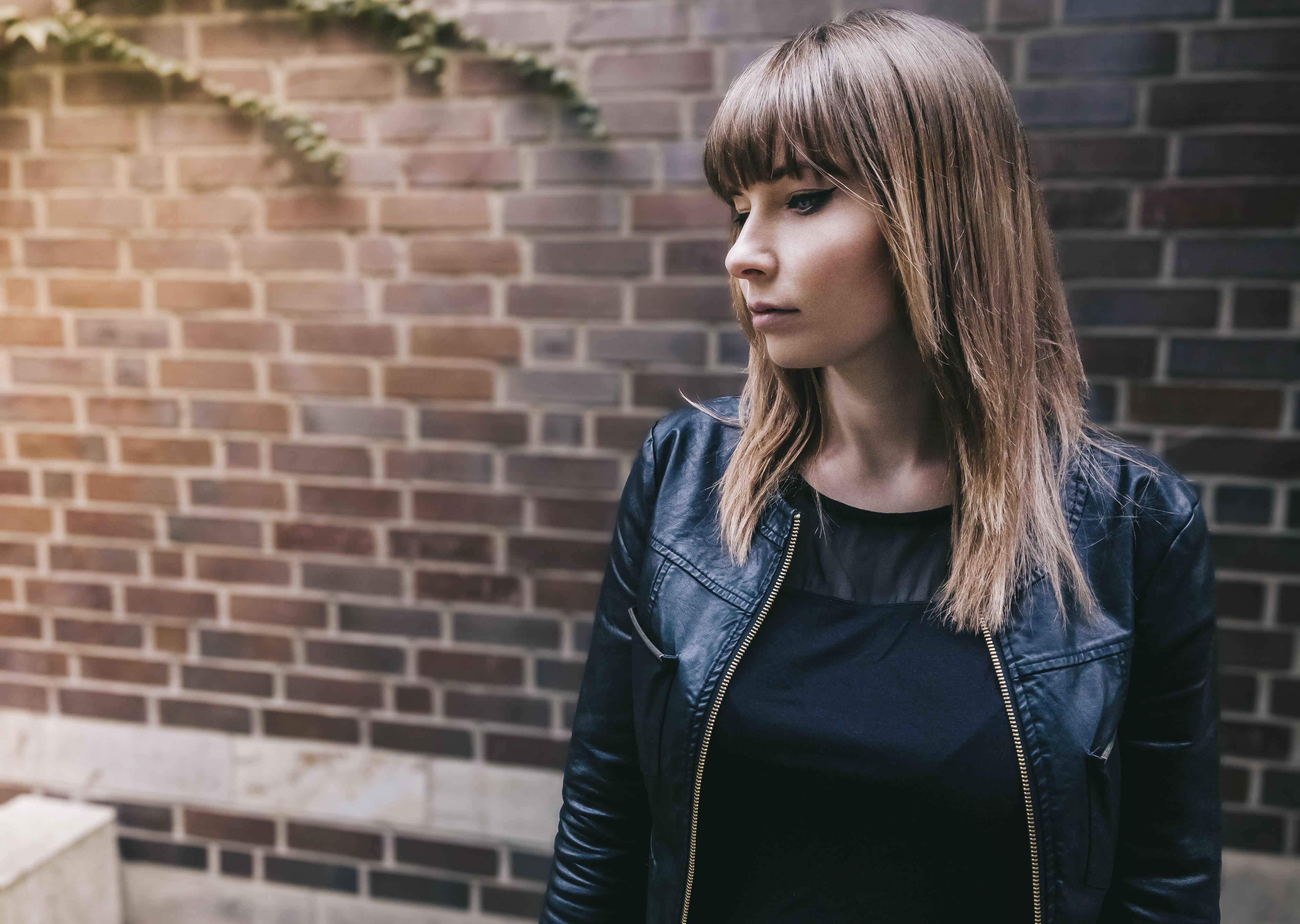 woman wearing black jacket standing beside concrete brick wall