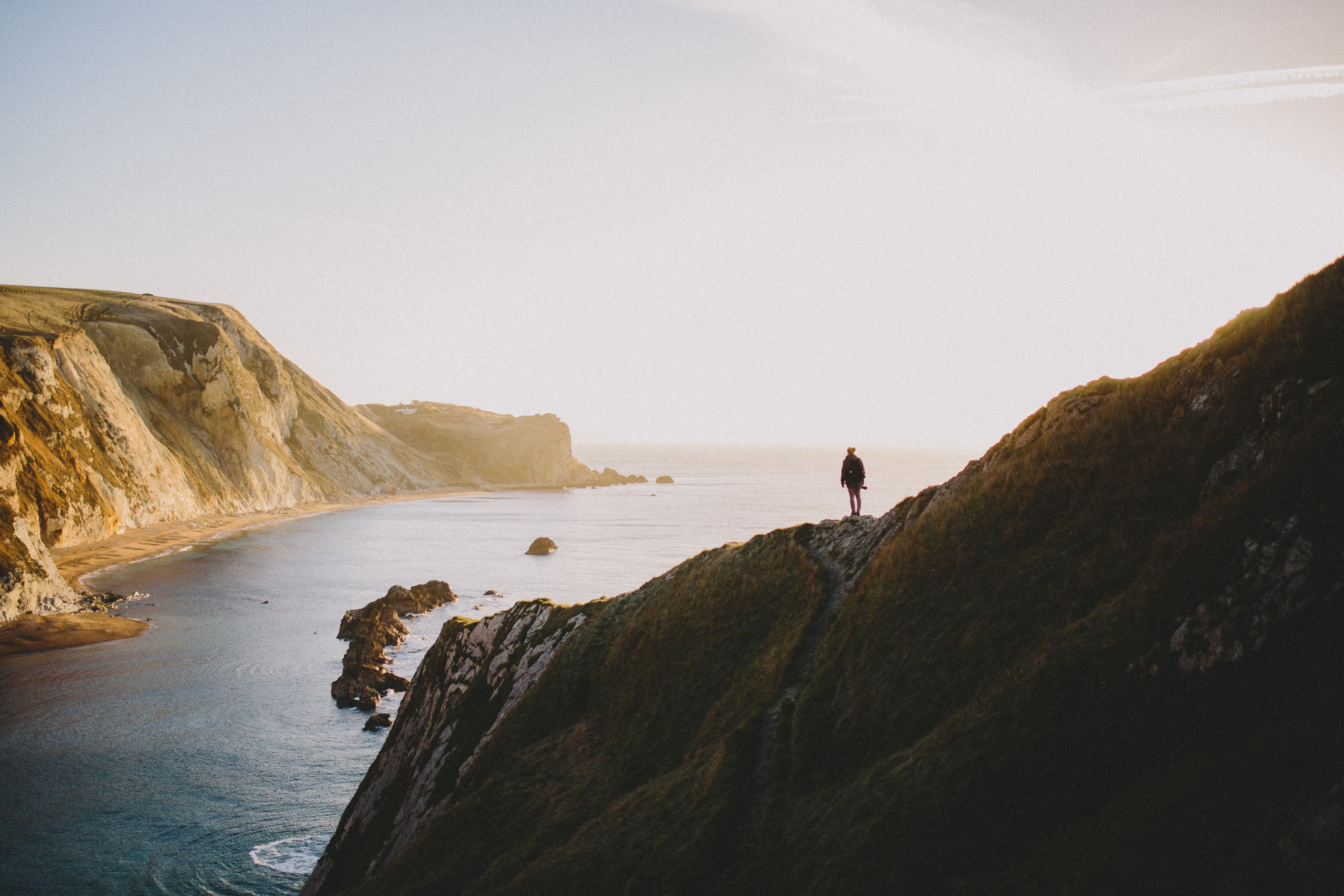 Person standing on the cliff overlooking the bay at the Durdle Door