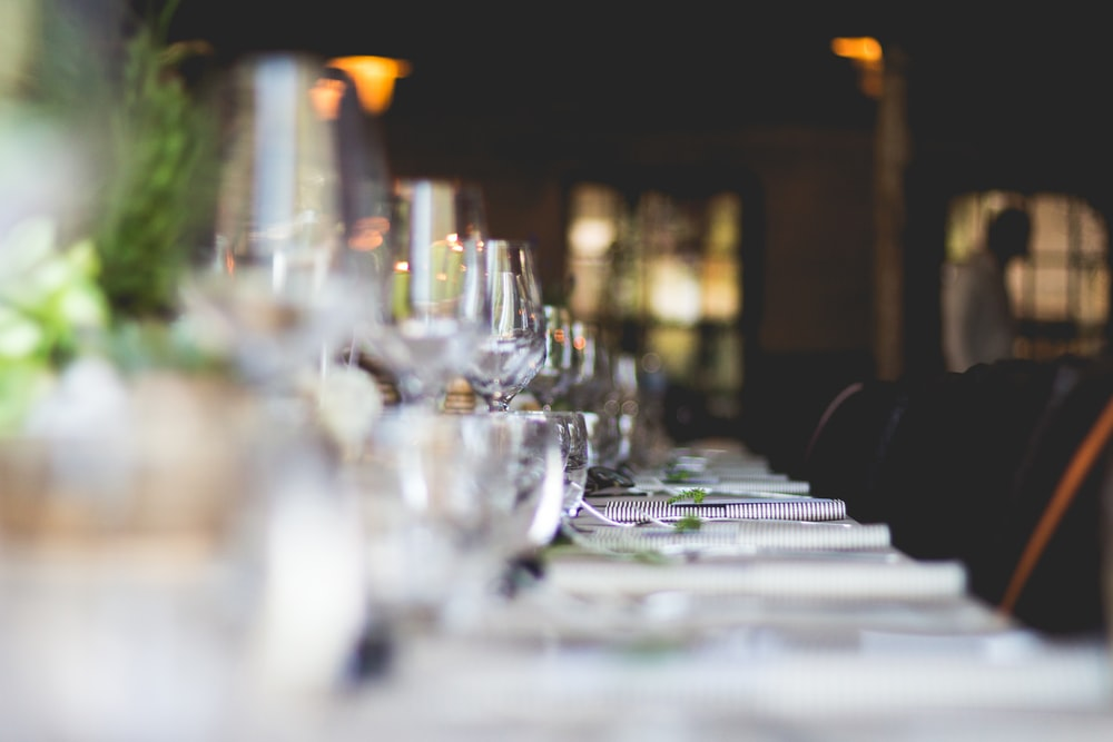 focused photo of wine glasses lined on table