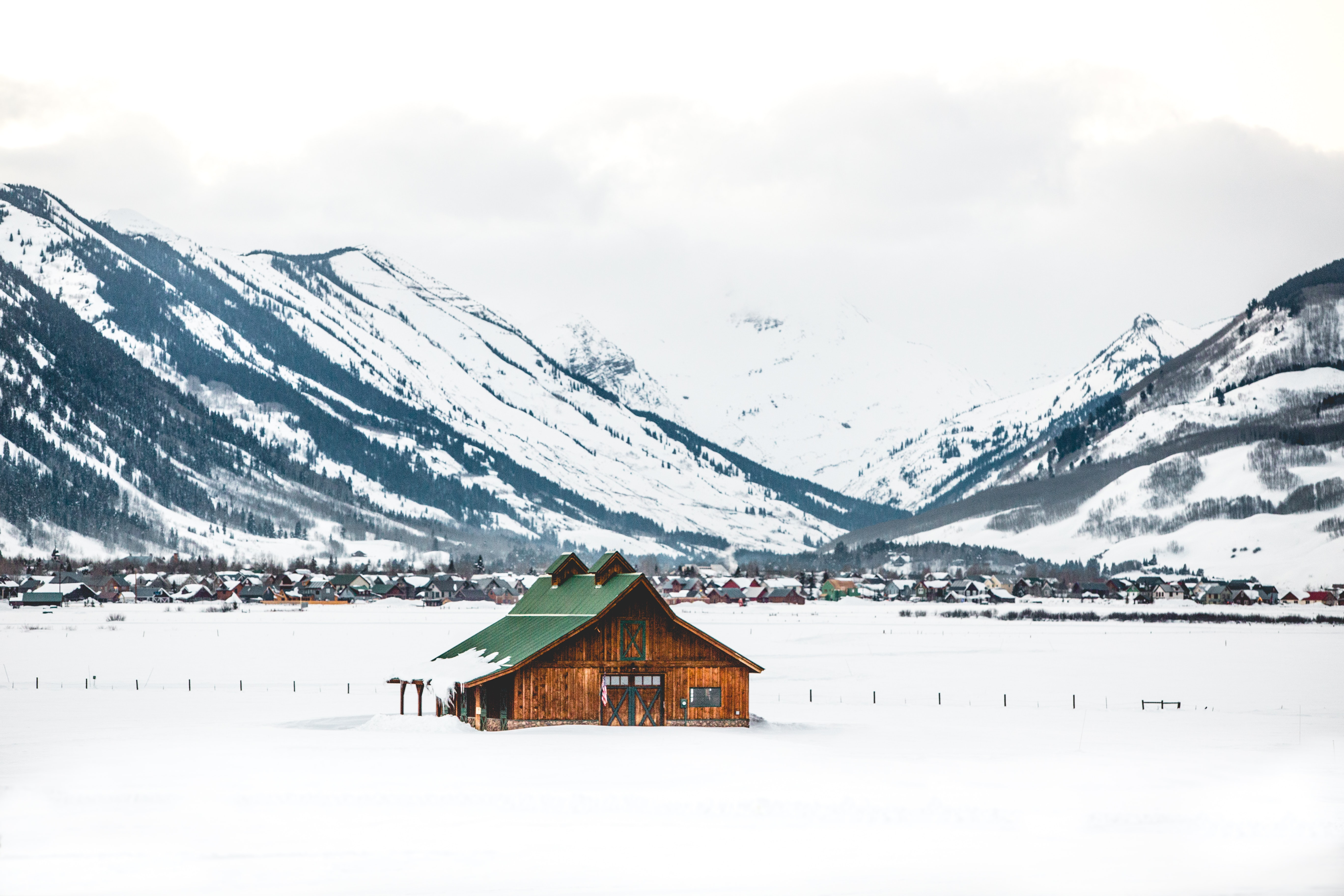 brown and green warehouse on snow covered field near mountain
