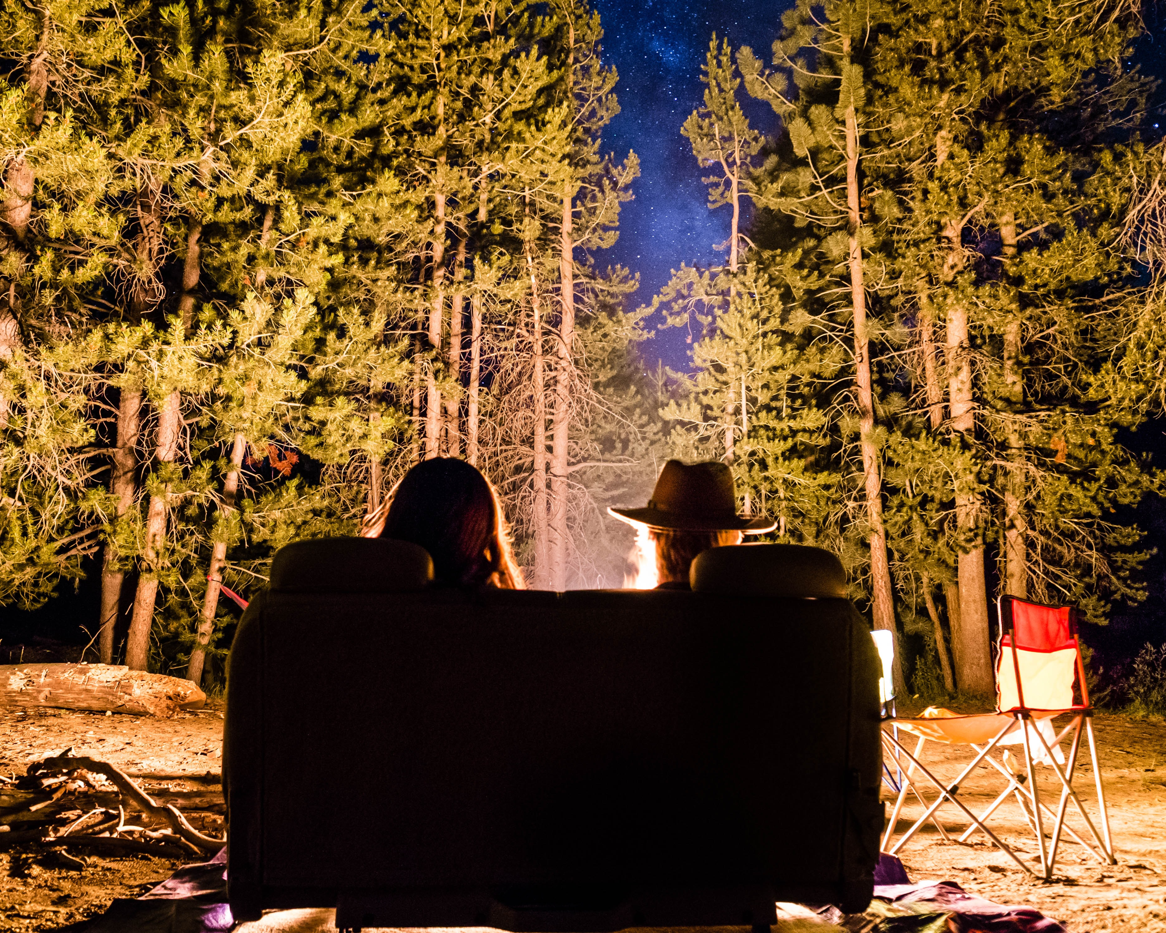 Two people seated in a sofa near a campfire in a forest at night