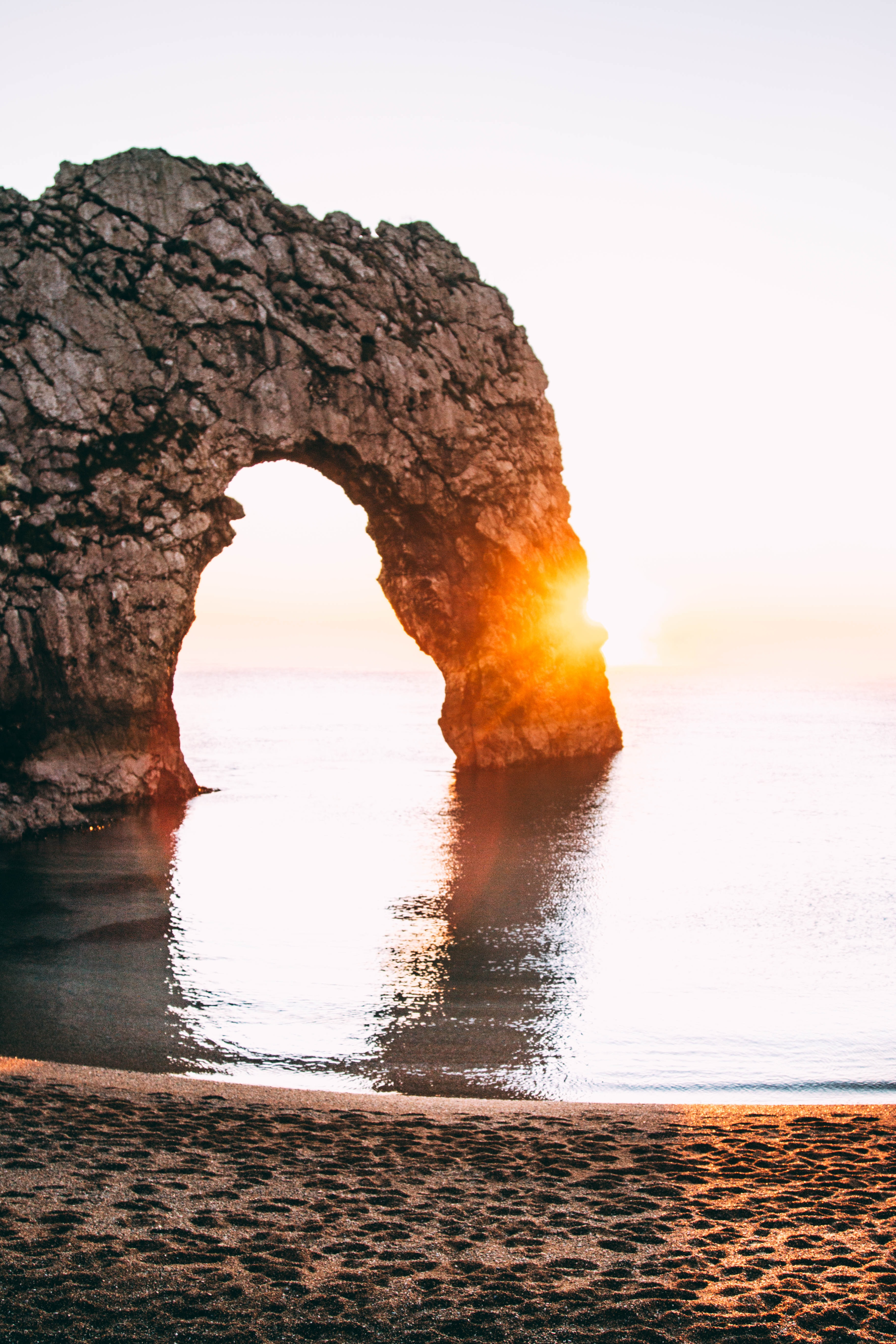 A natural rock arch is illuminated with the rays of a golden sunset over the water near the shoreline of Durdle Door.