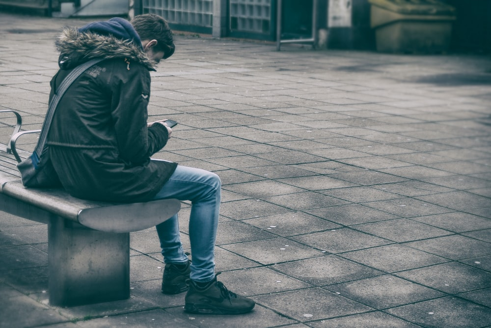 man sitting on bench holding phone