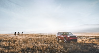 red suv on field and three person riding horse cowboys teams background