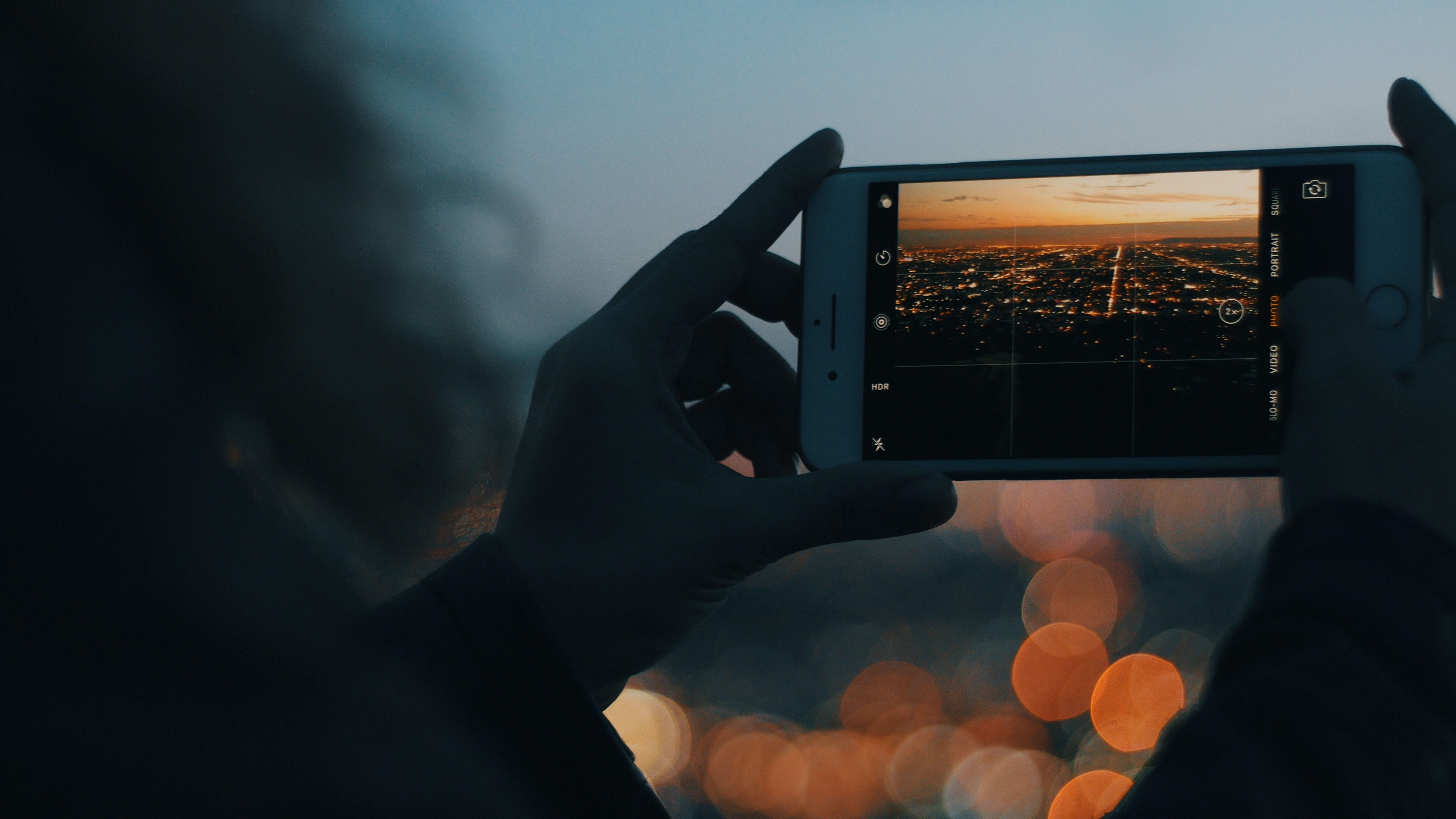 person capturing photo of city using iPhone during orange sunset