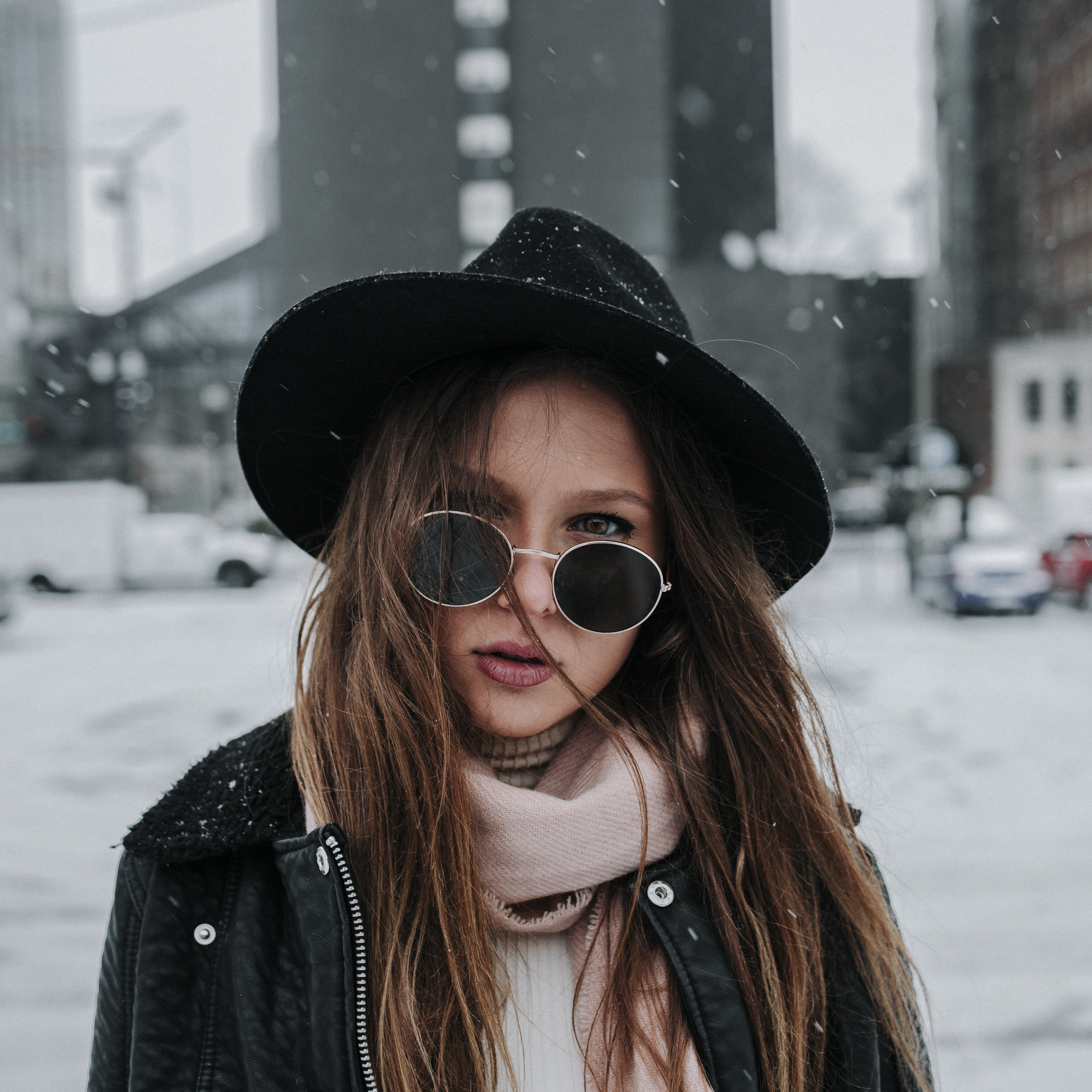 A brunette woman wearing a hat and sunglasses standing in the snow in Nashville