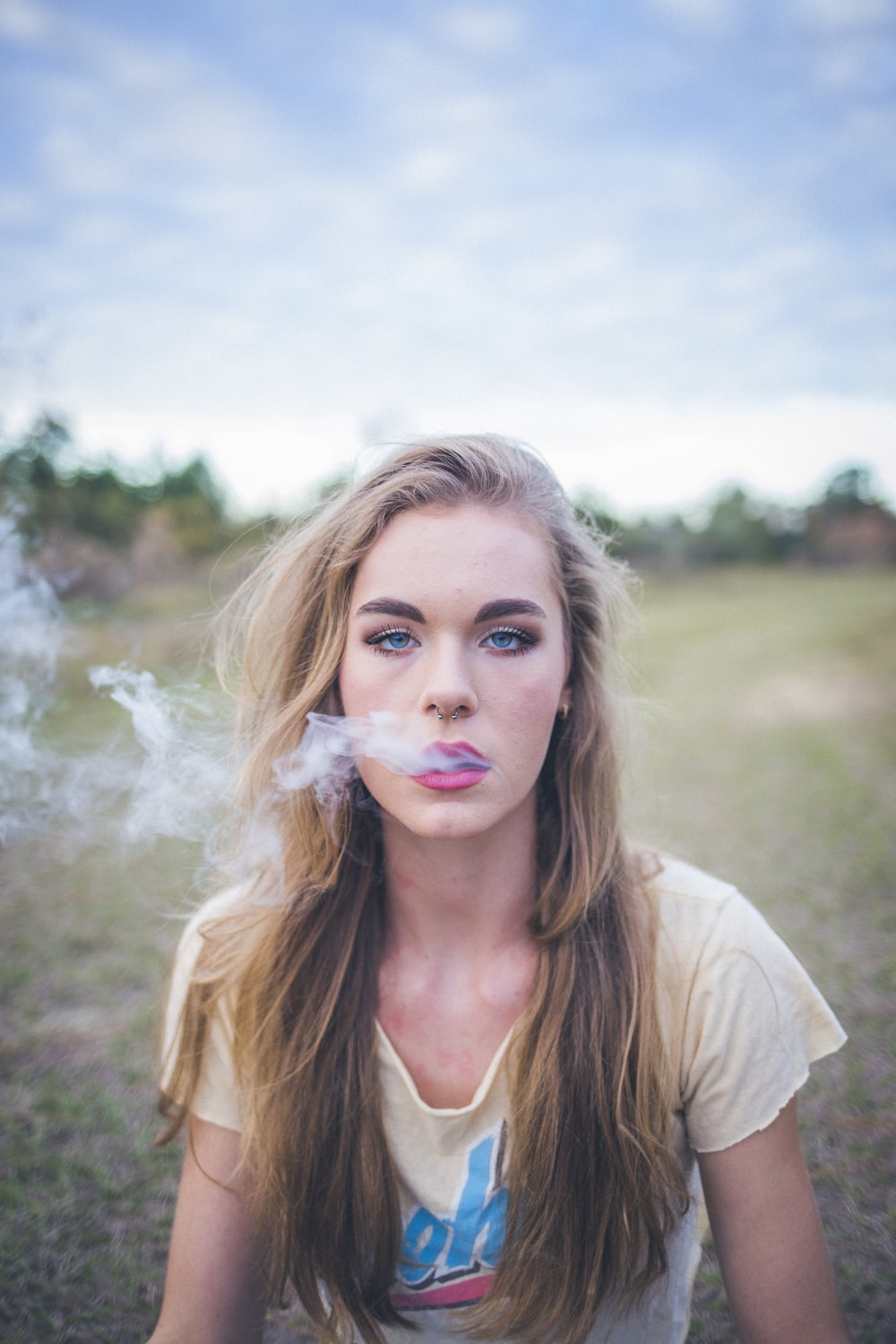 woman smoking while sitting on green grass