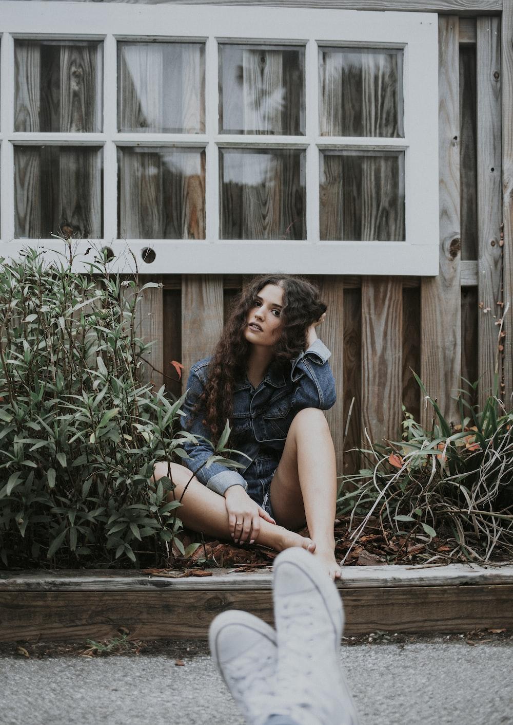 woman sitting under white wooden window