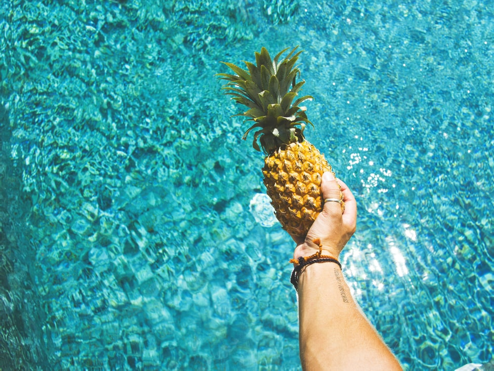 person holding yellow pineapple