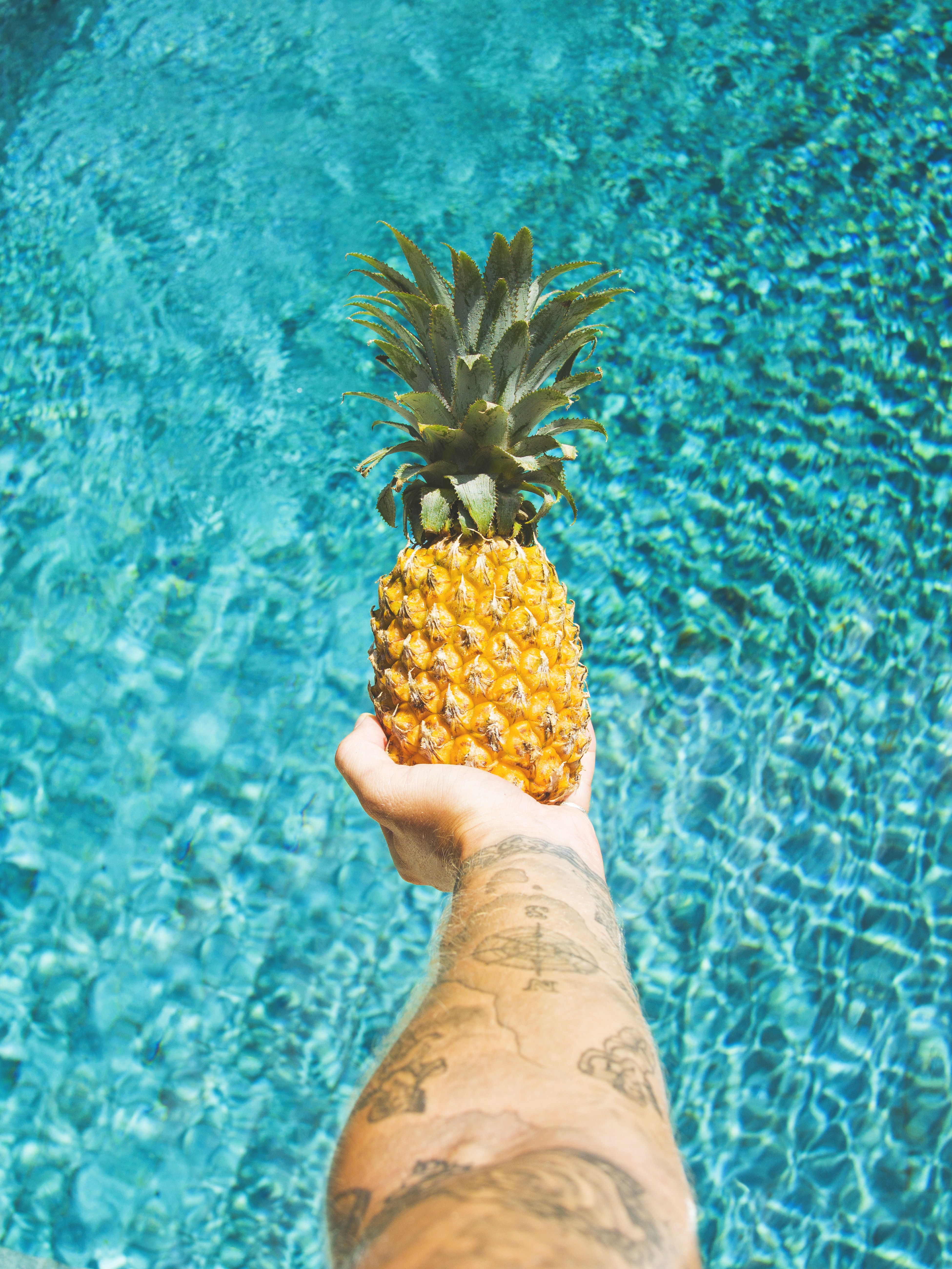 person holding pineapple fruit