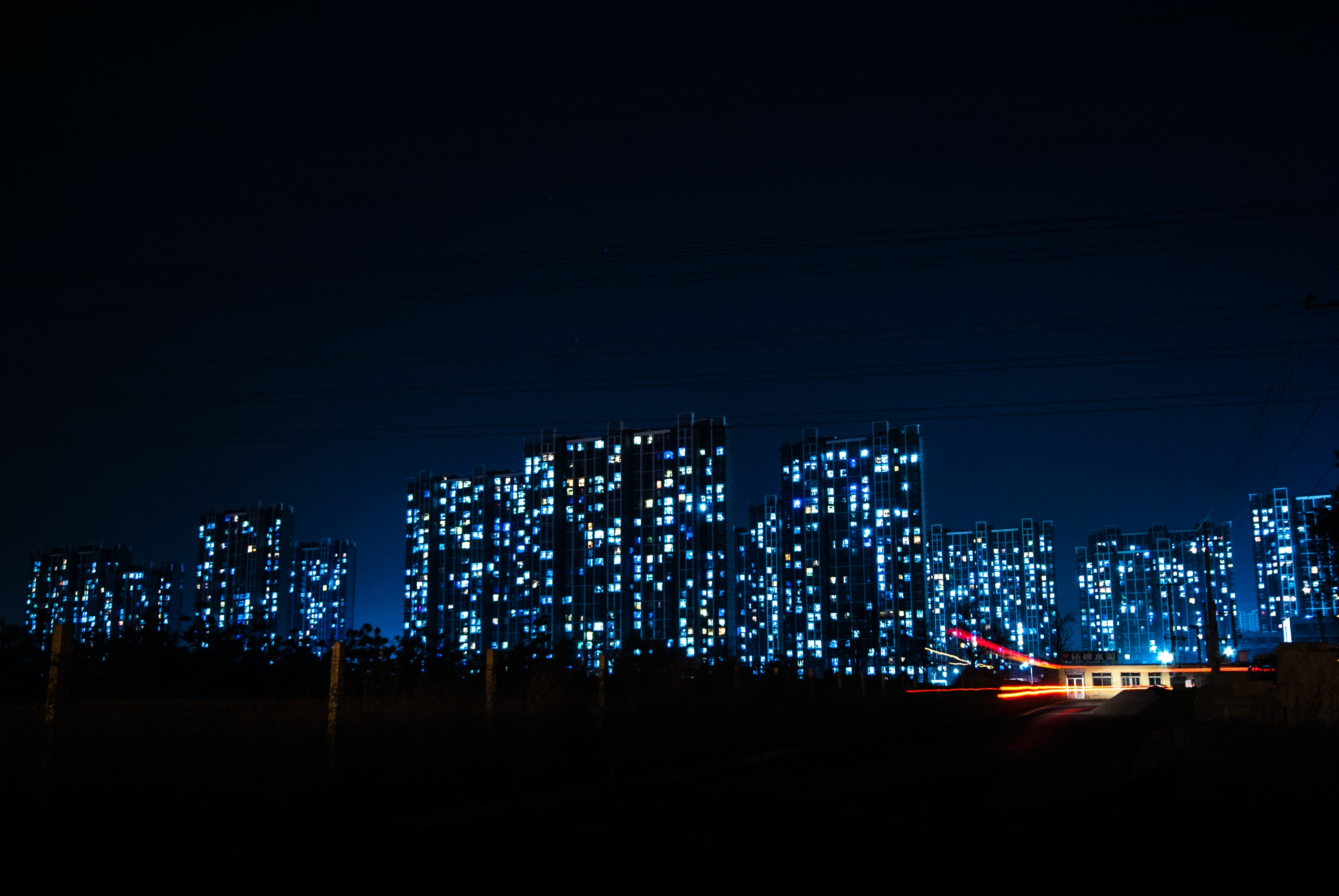 An illuminated city with more than half a dozen large buildings and skyscrapers with blue lights in the background