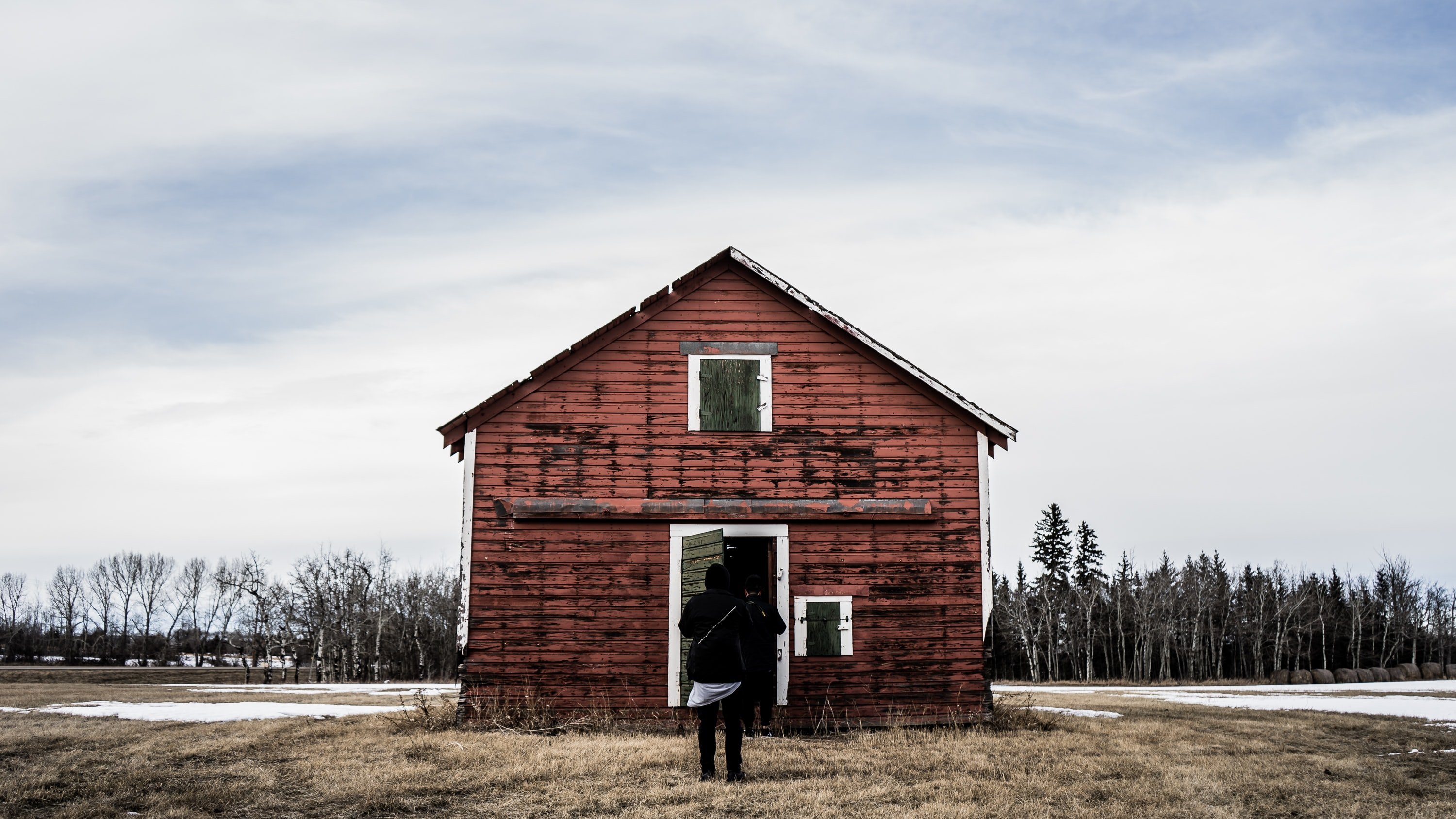 Two people in front of a barn on a winter's day