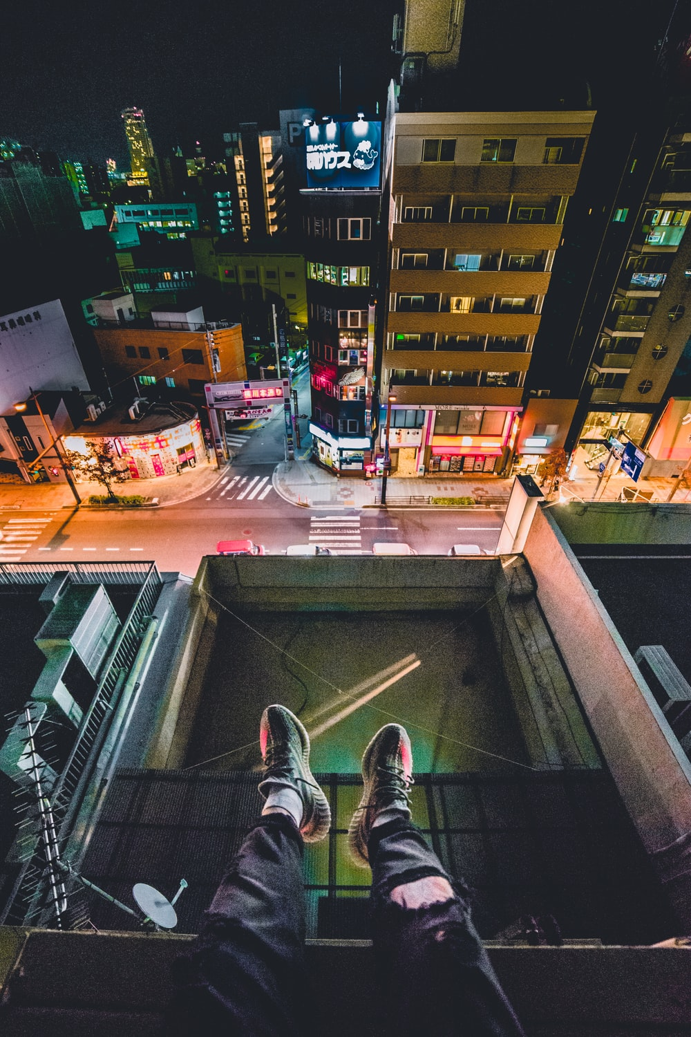 man sitting on rooftop overlooking city