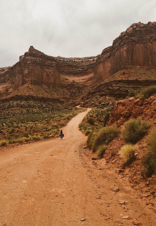 person walking on walkway near mountains