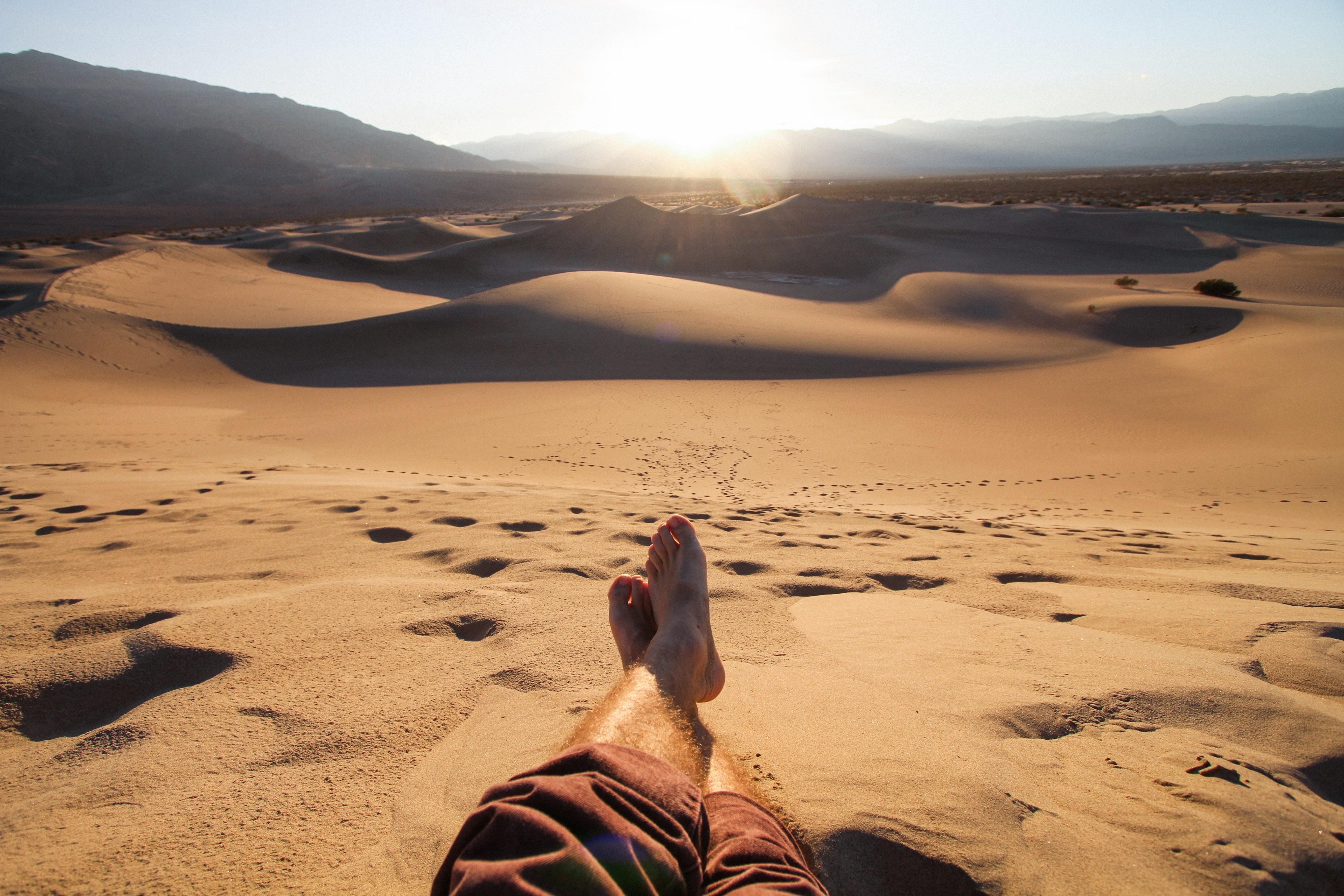 man sitting on desert during daytime