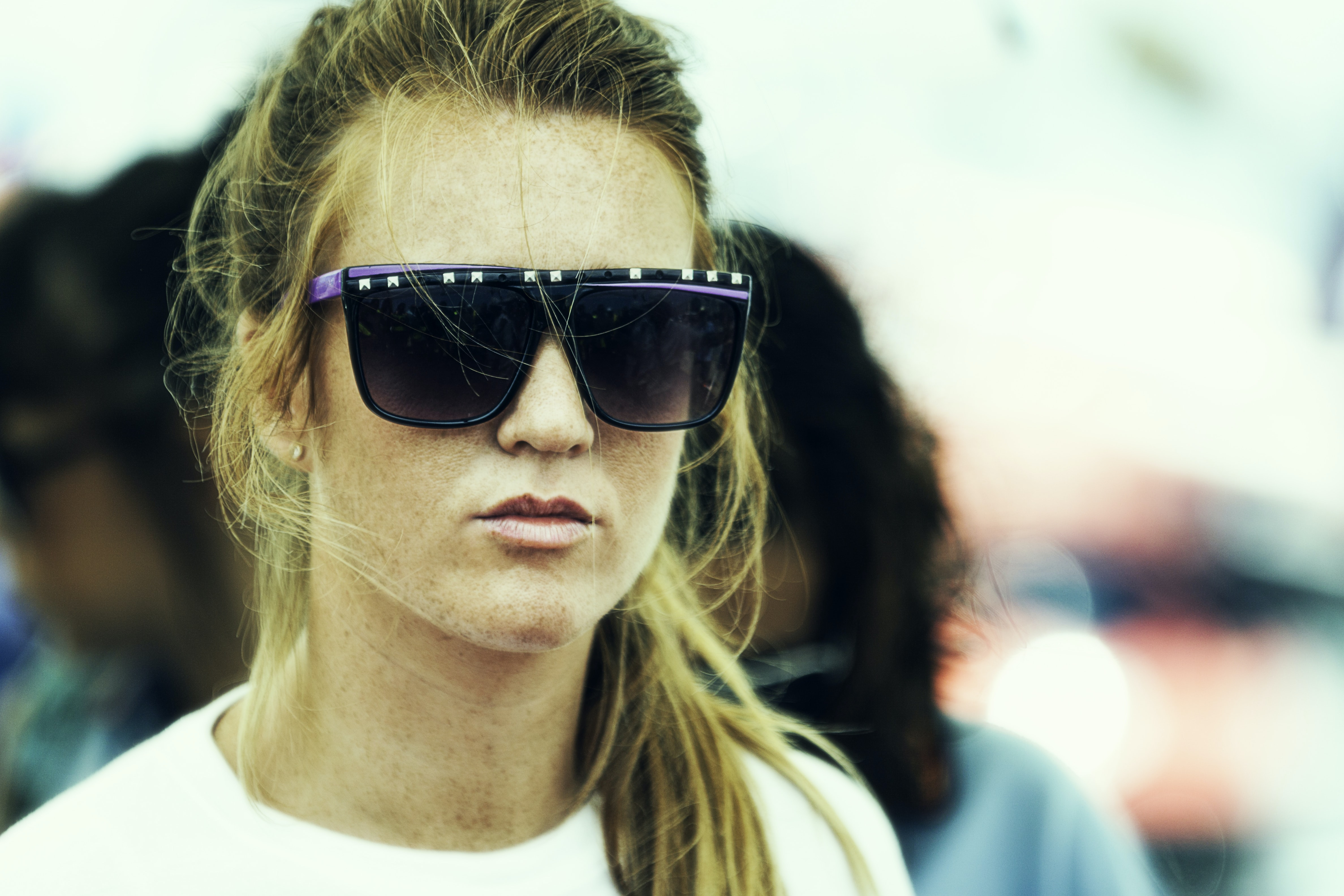 A woman with a ponytail wears large sunglasses against a blurry background