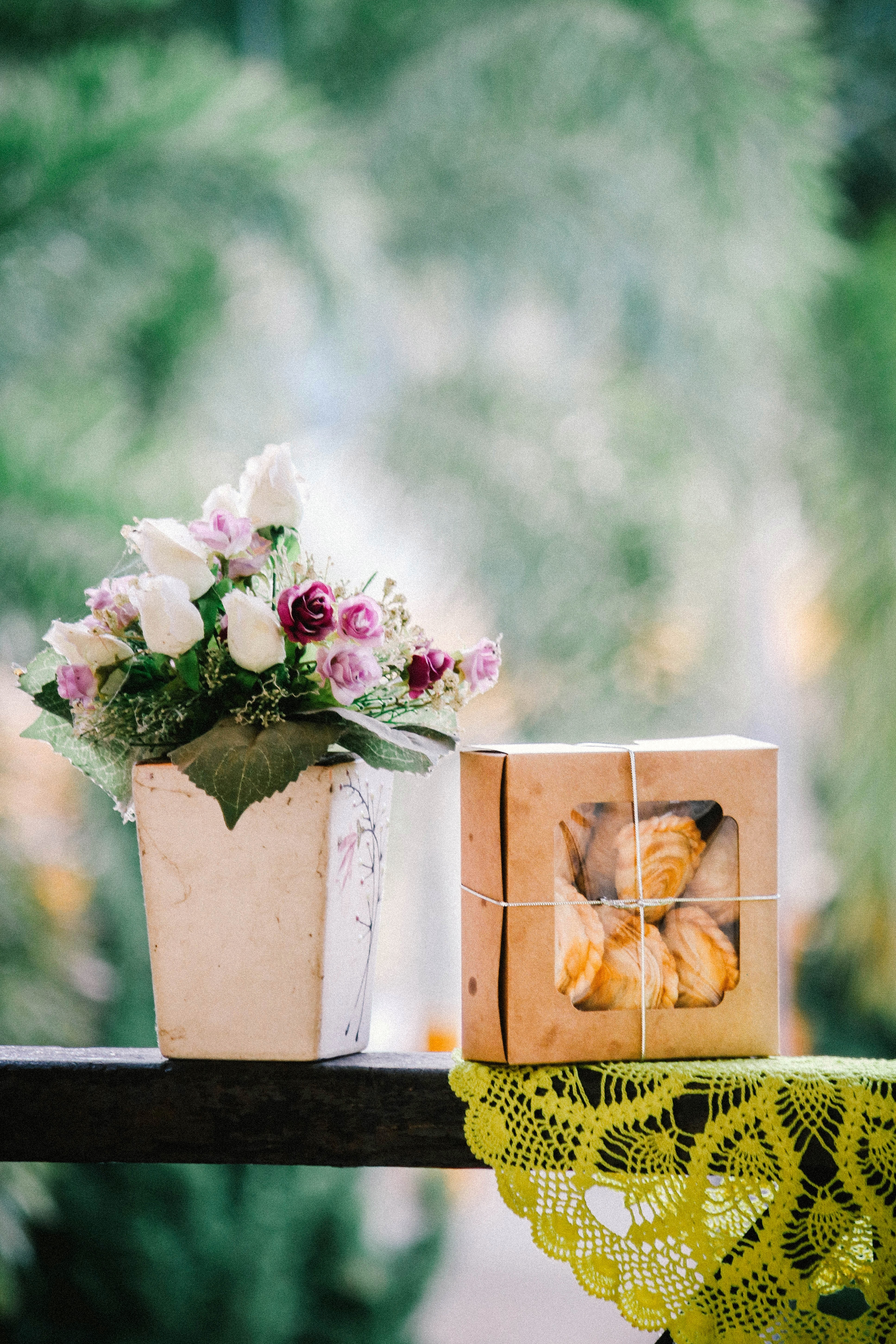 white rose bouquet in ceramic vase on wooden fence