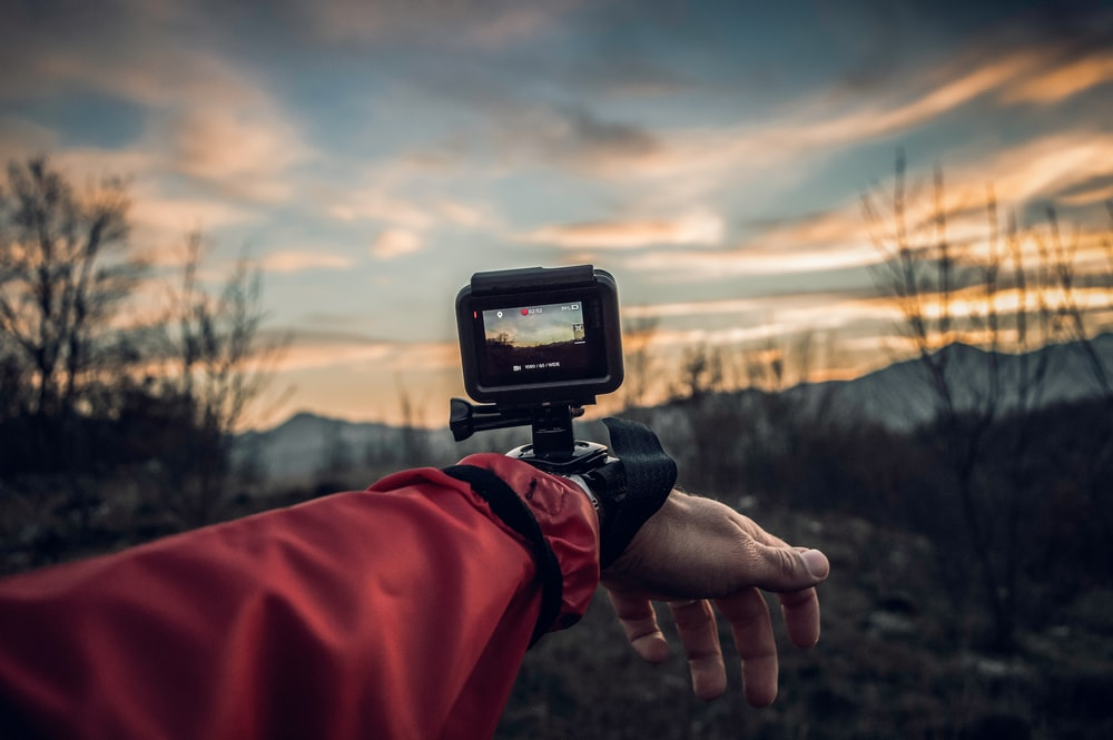 A camera strapped to a person's wrist near bare trees