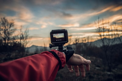 person carrying action camera gopro teams background