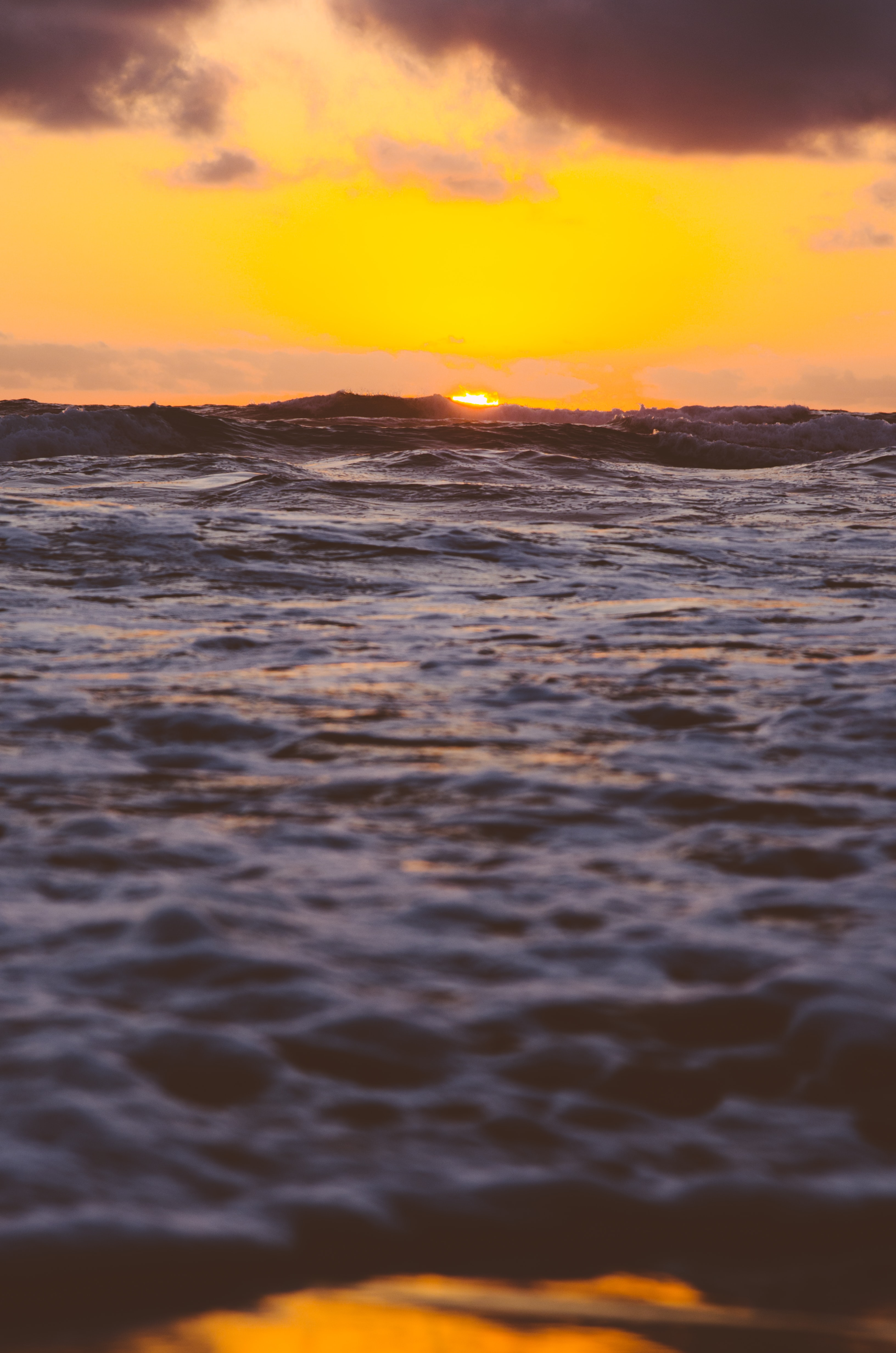 An orange sky at sunset over the waves of the ocean at Venus Bay