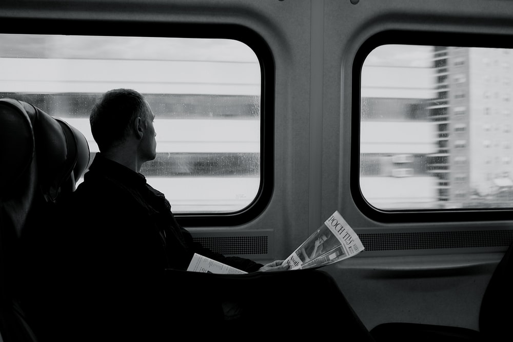 man inside train looking on window while holding newspaper grayscale photography