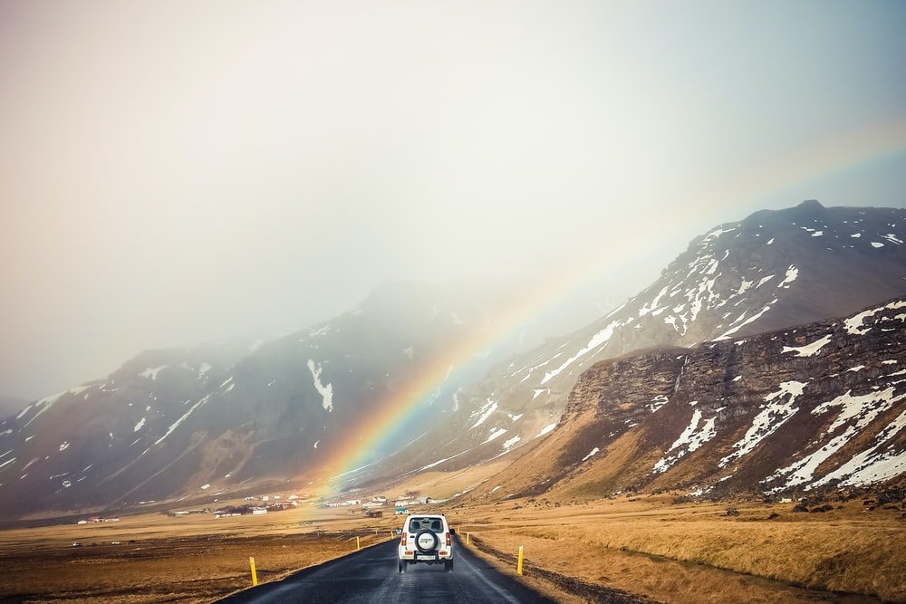 white car travelling near mountains with rainbow