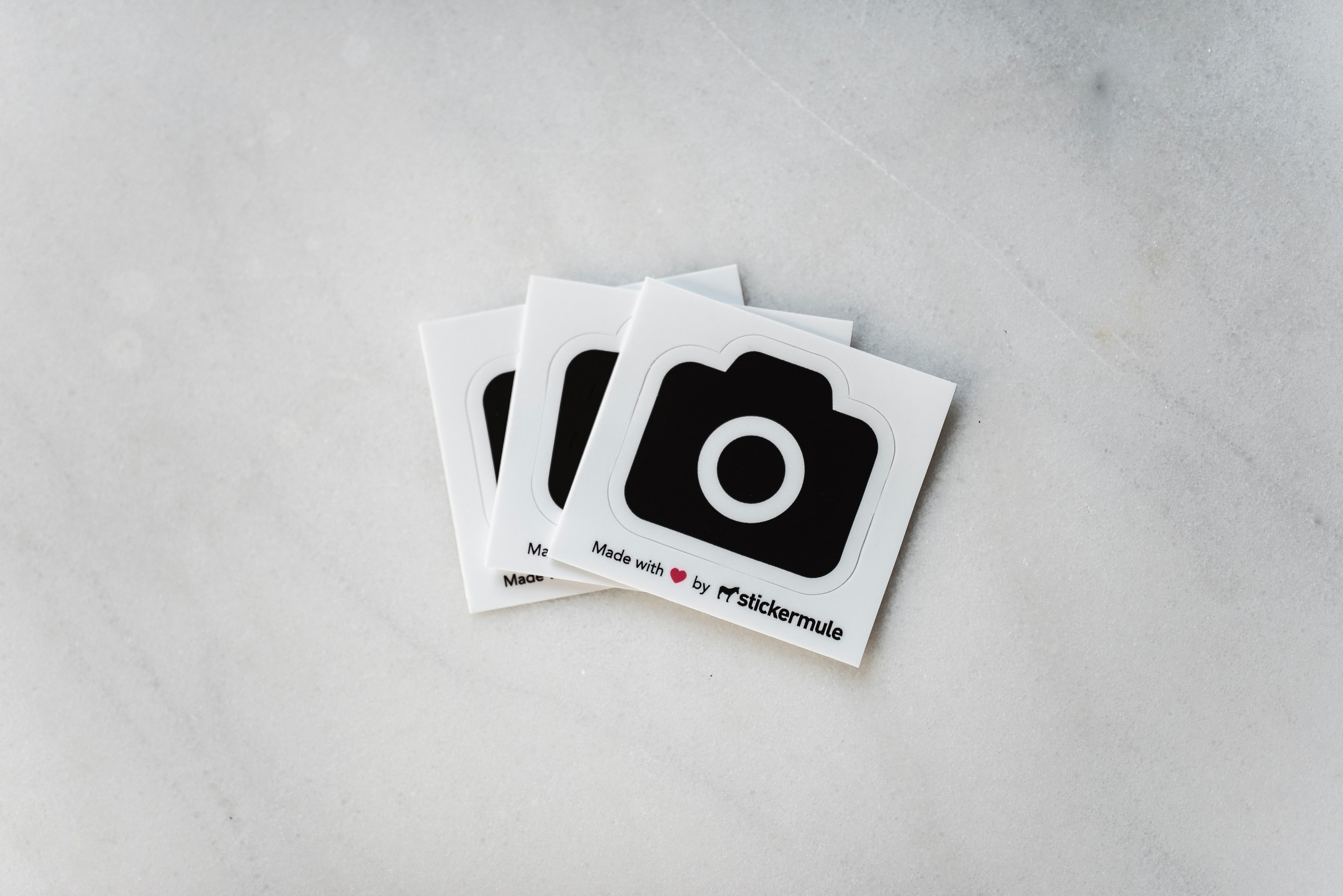 Stickermule stickers for Unsplash on a marble table