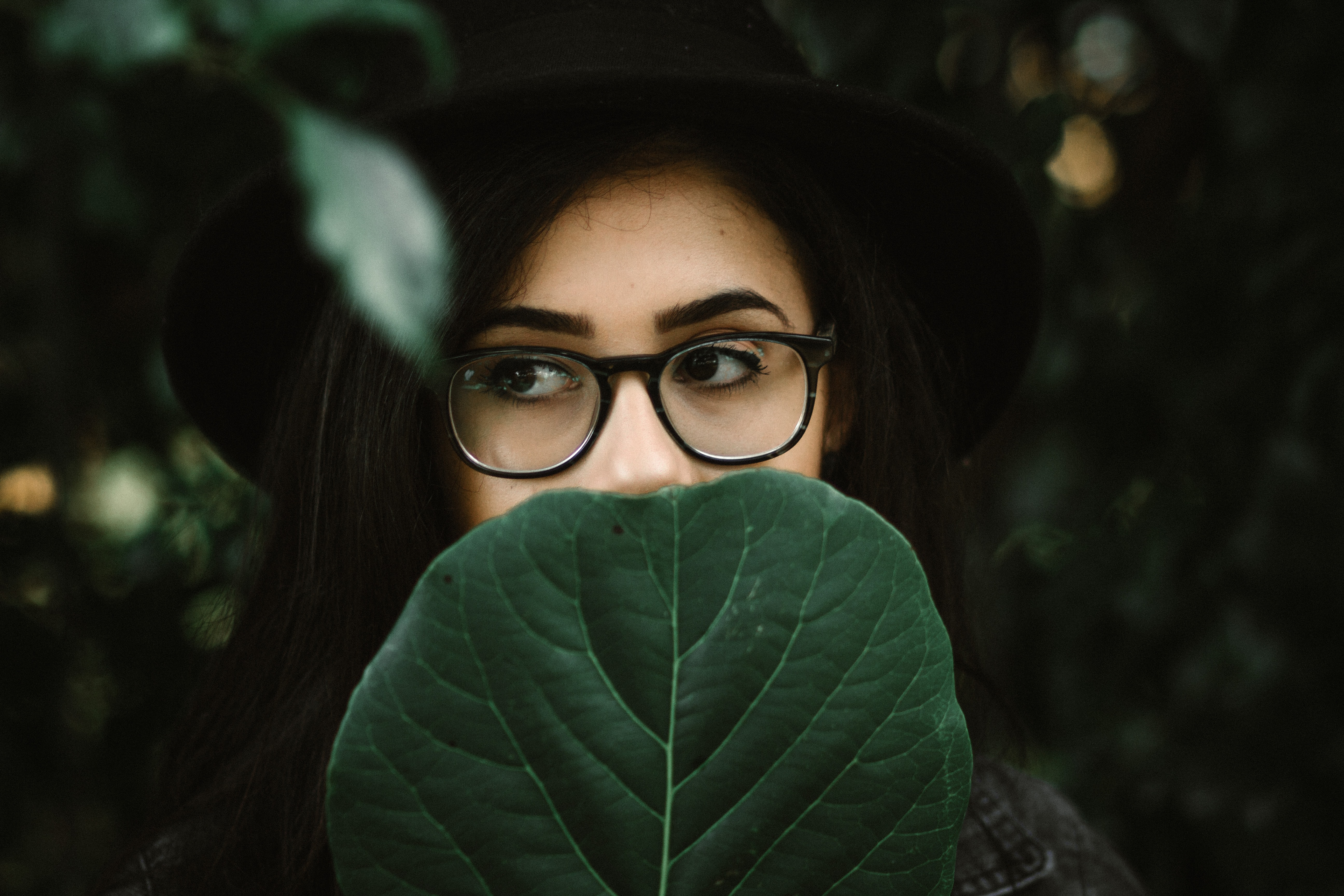 Woman with bold eyebrows and thick rimmed glasses behind a leaf