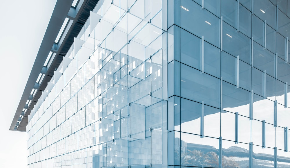 architectural structure photography of glass building under cloudy sky