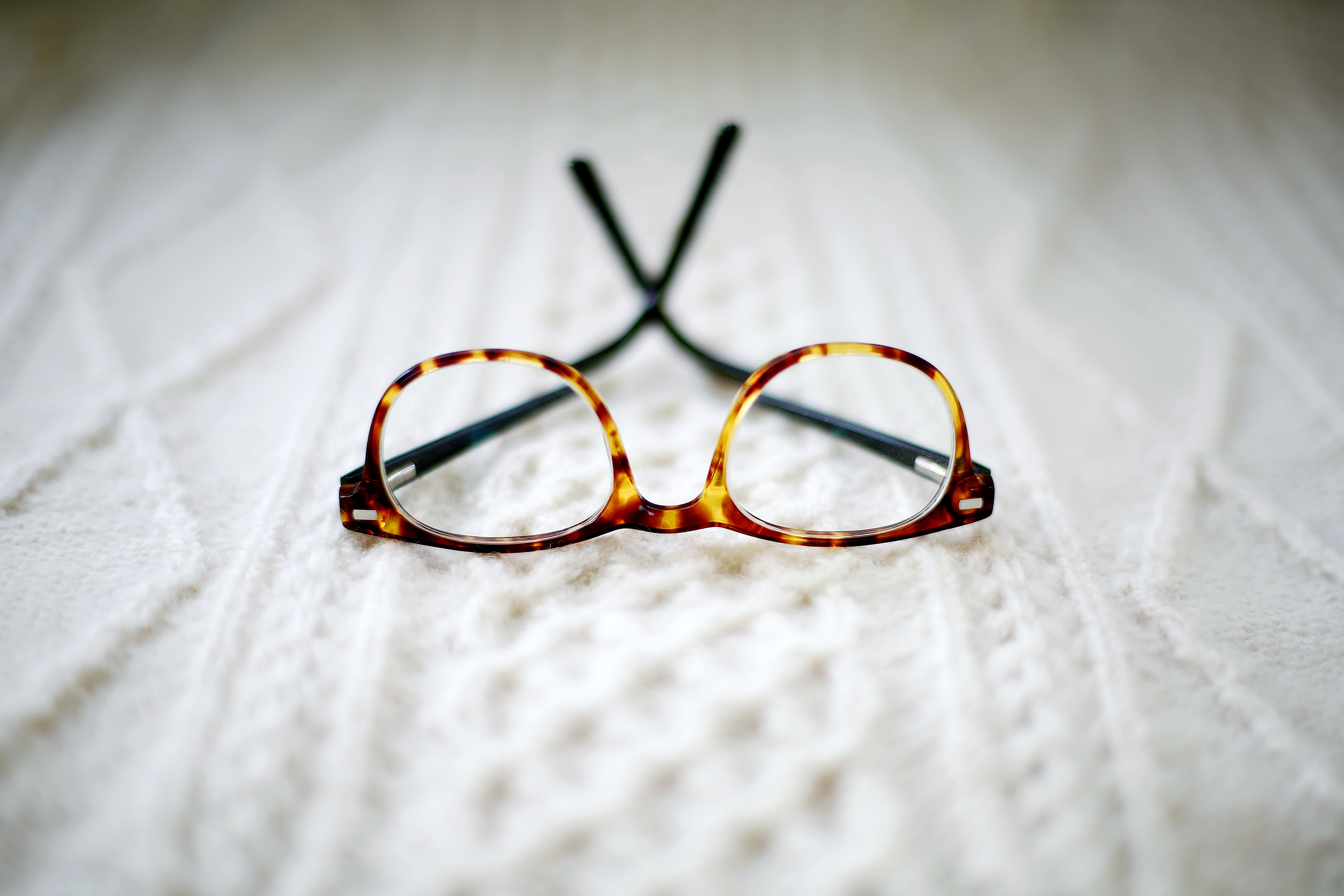 A pair of yellow speckled glasses resting upside down on a patterned white fabric