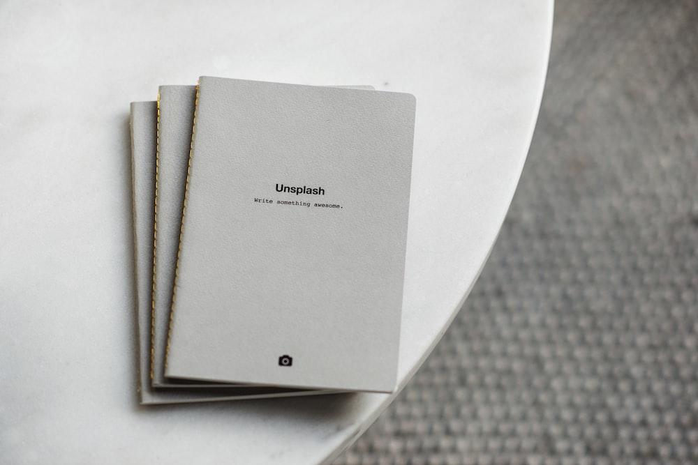 three white softbound books on white surface