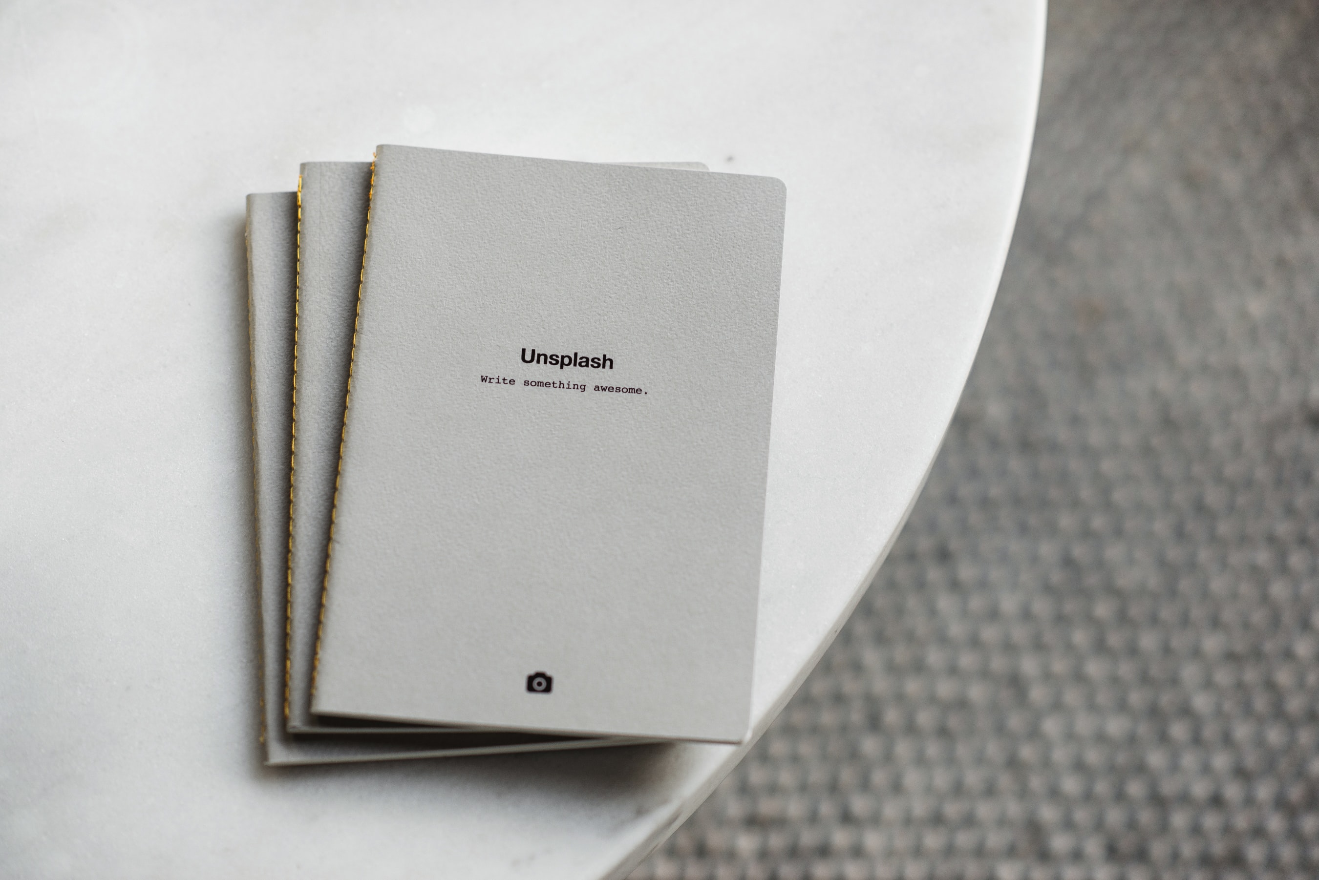 Gray Unsplash notebooks on a white round table