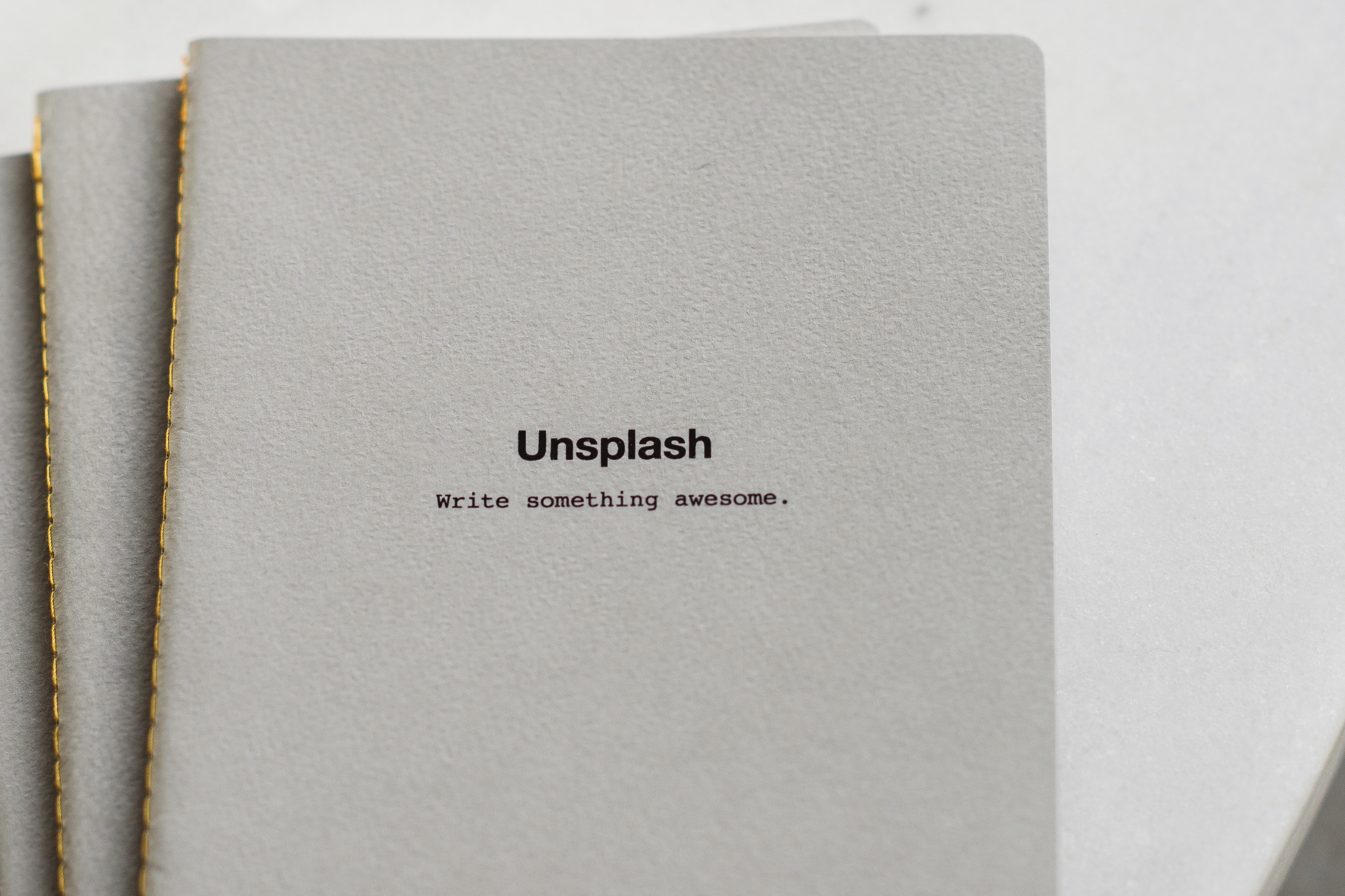 """Unsplash notebooks that read """"Write something awesome."""" with gold colored bindings on a white table."""