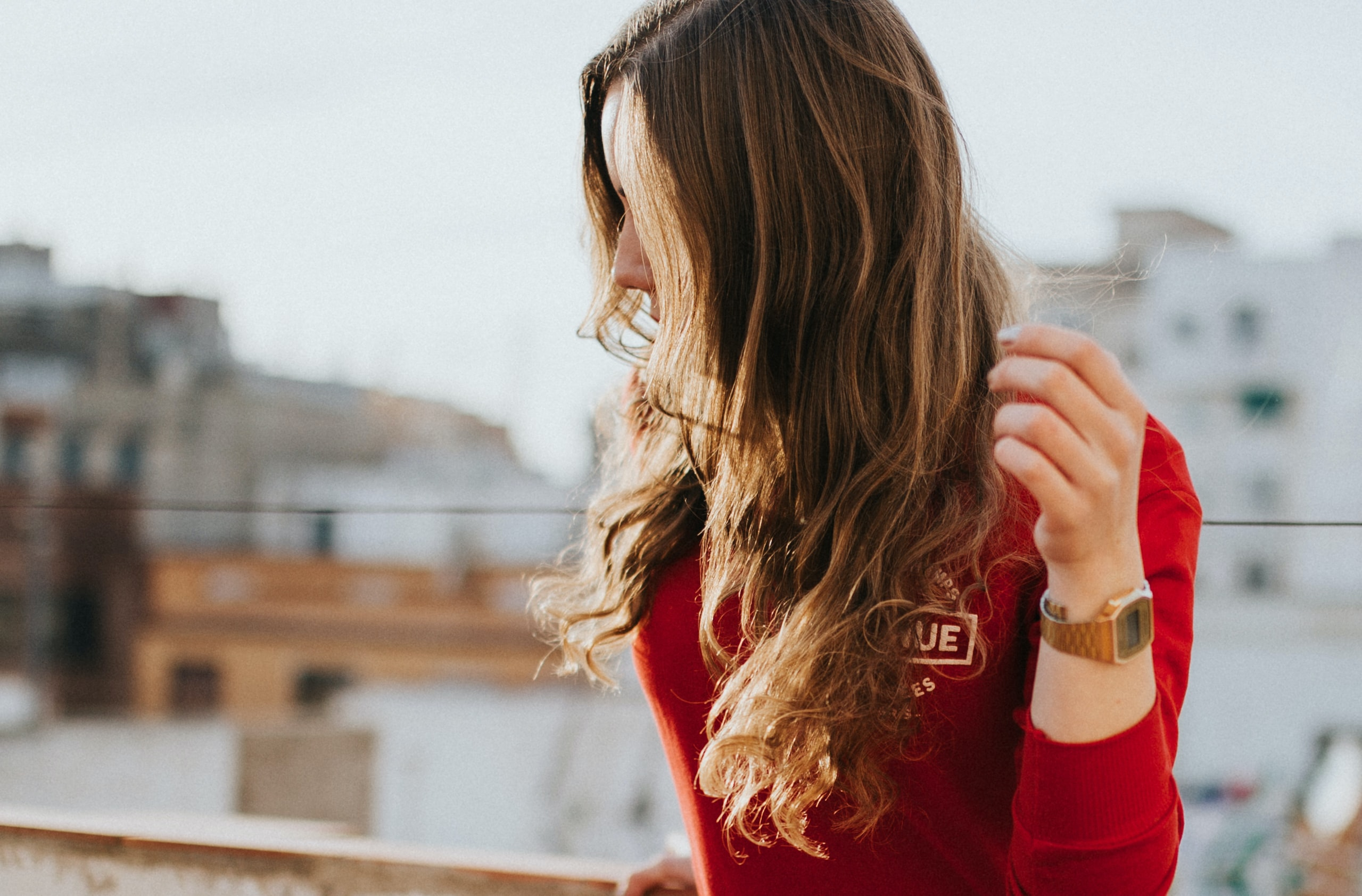 A woman in a red sweater with her hair obscuring her face outdoors