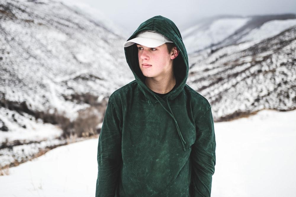 man wearing green drawstring hoodie and white cap