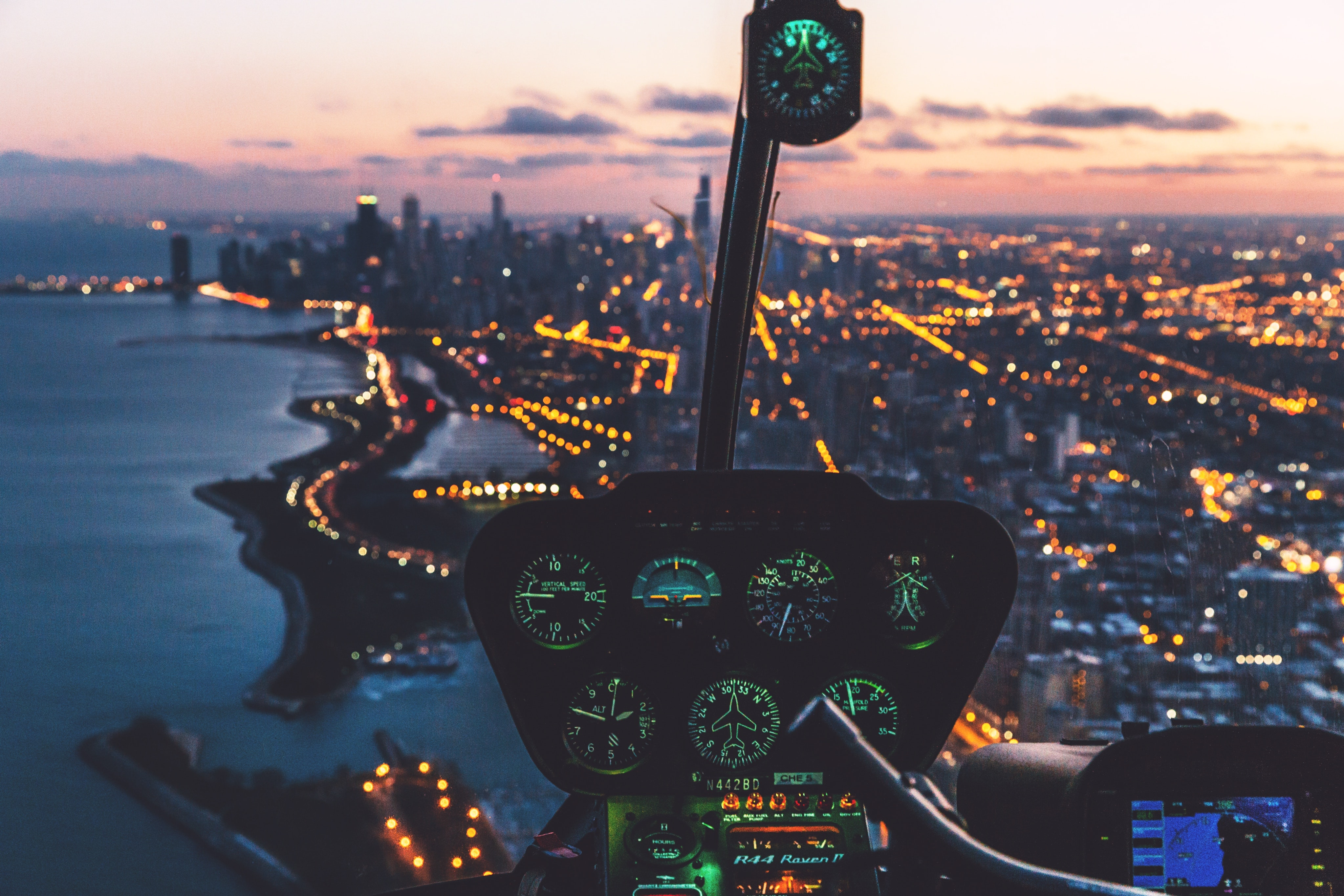 Dashboard of helicopter flying over a city with skyscrapers at dusk