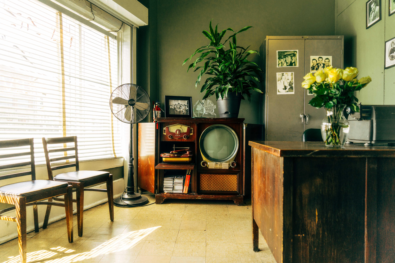 grey pedestal fan near brown wooden rack inside house