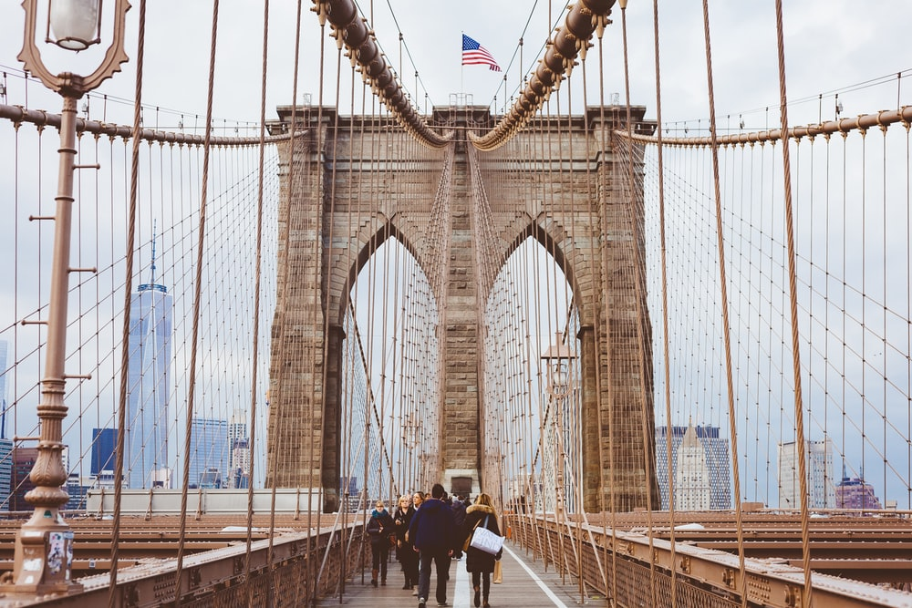 people walking on Brooklyn Bridge during daytime