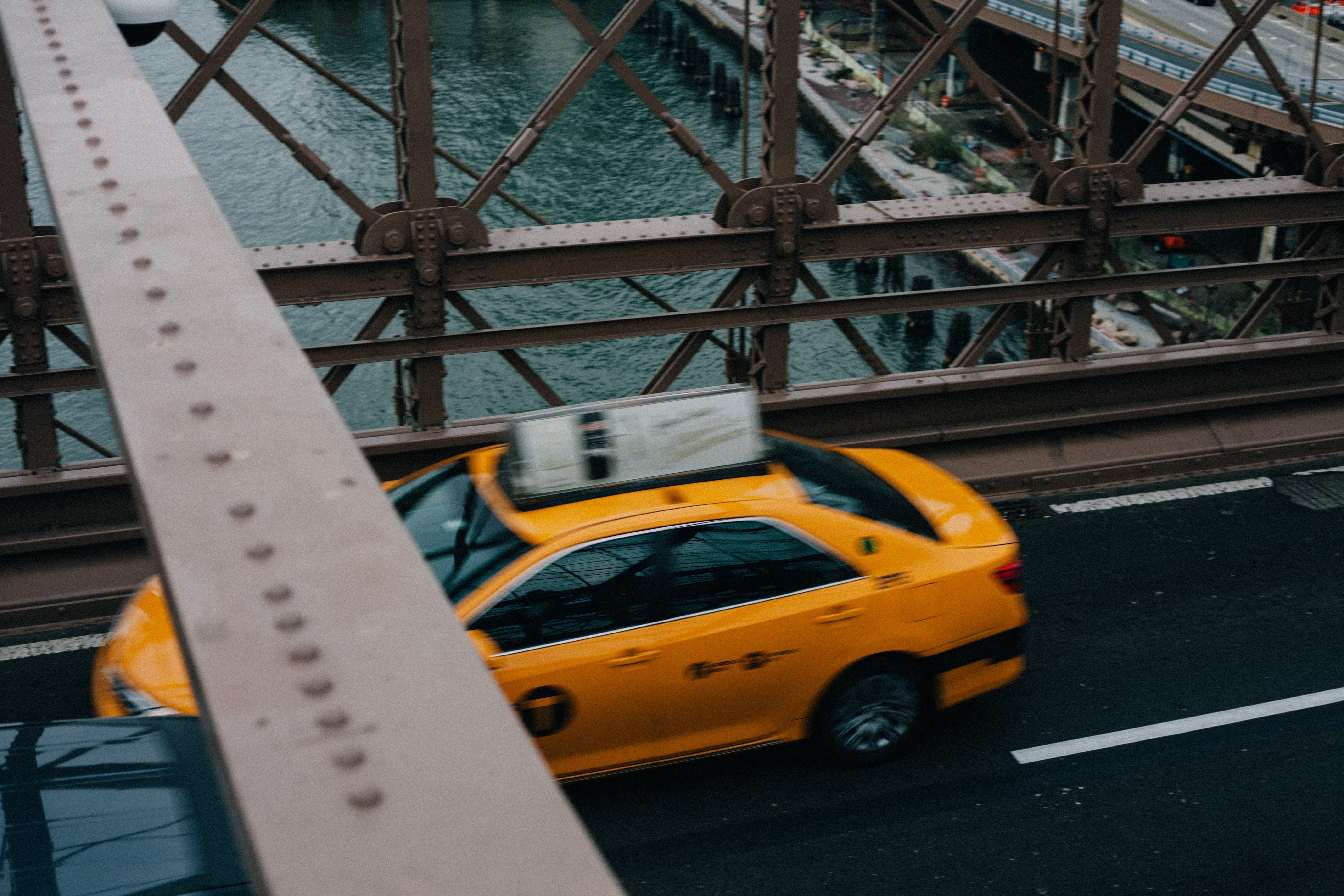 A high view of a yellow taxi cab driving on a bridge