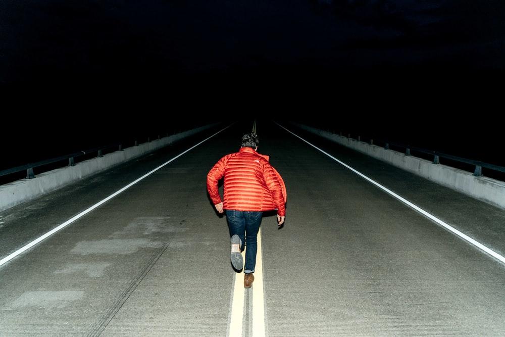man running on road during night time