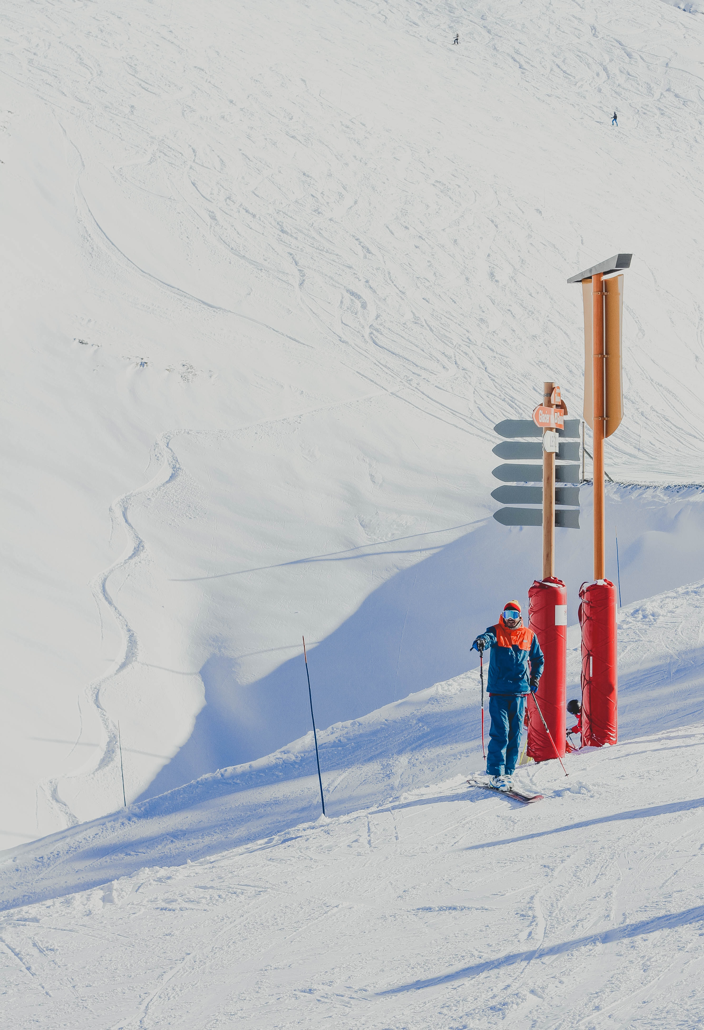 man in blue jacket holding ski poles standing near red and brown post