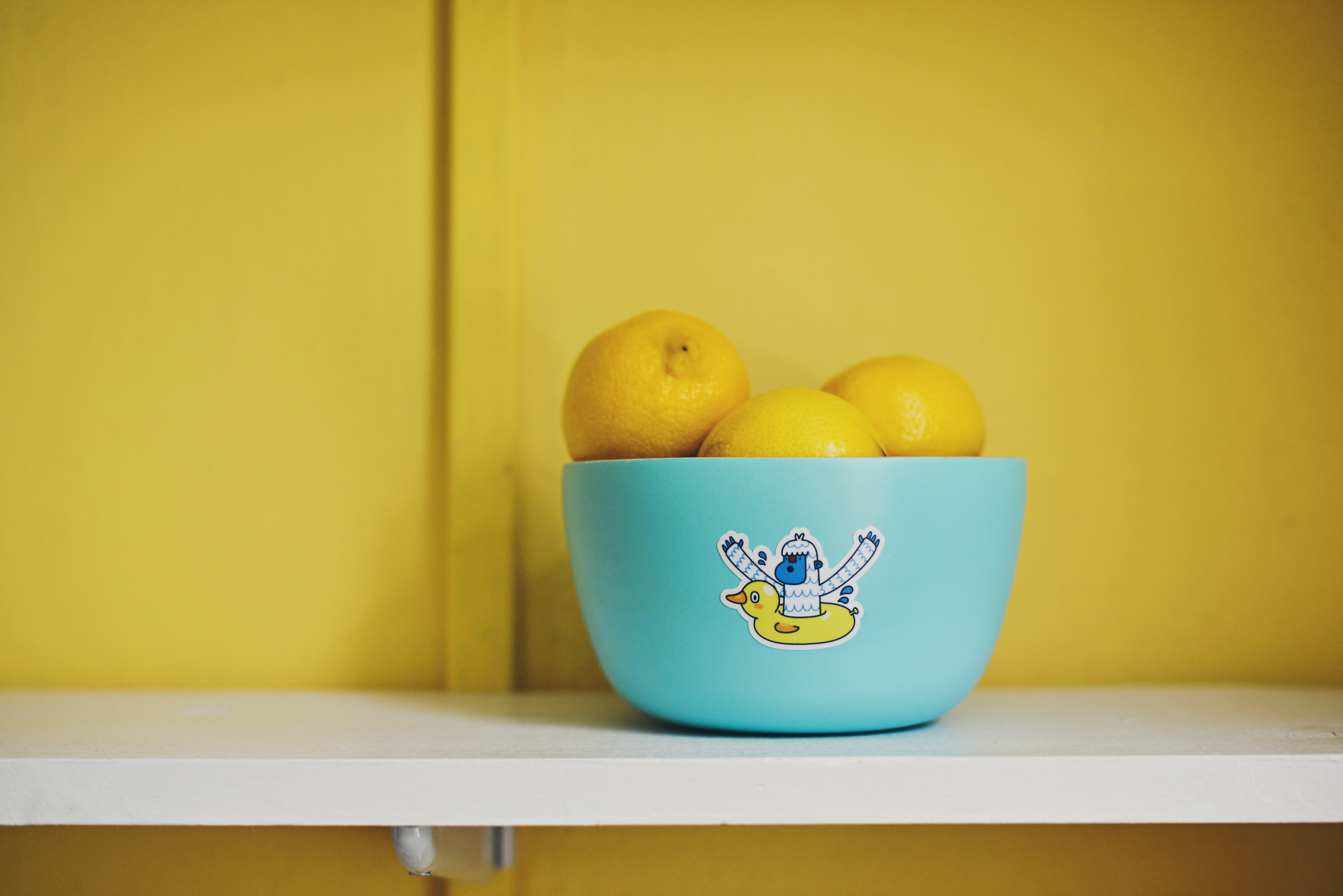 Lemons in a blue bowl with a sticker on it against a yellow wall