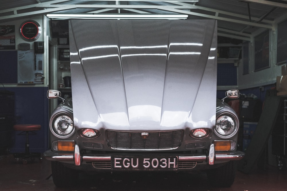classic silver car with it's hood opened and black EGU 503H license