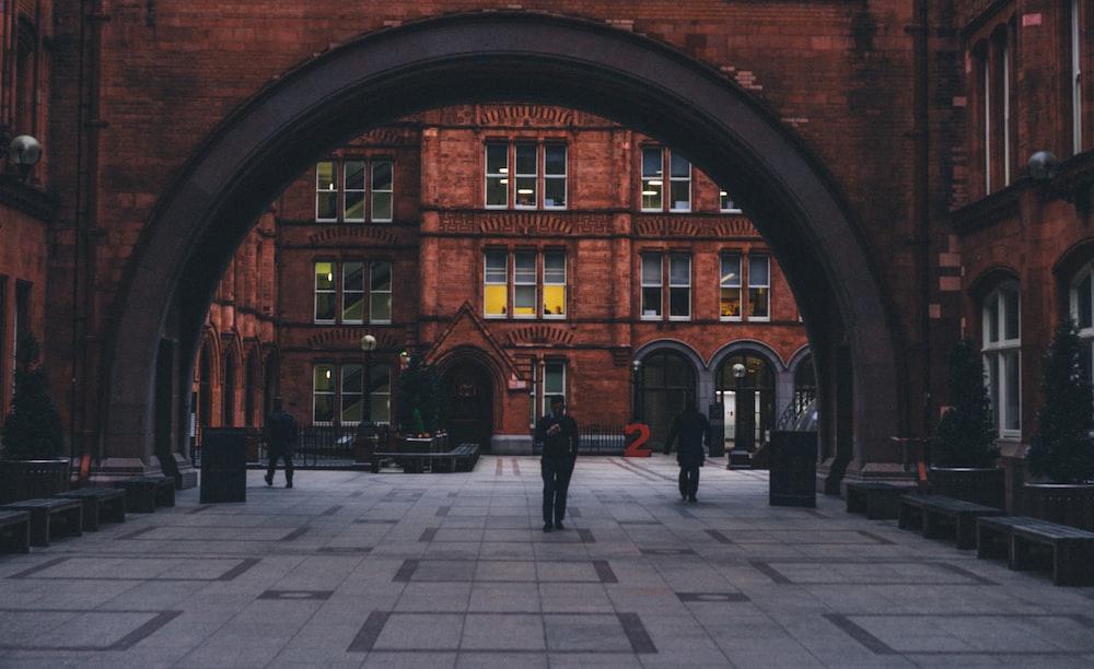 man standing under brown concrete building