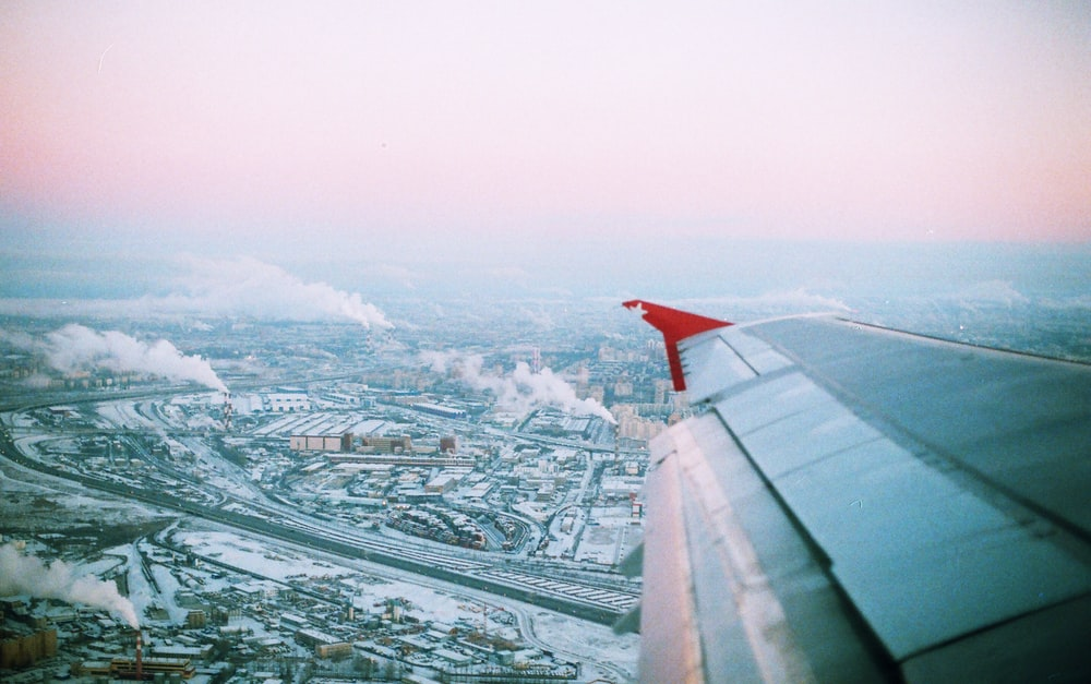 photo of flying airplane wing and city during daytime